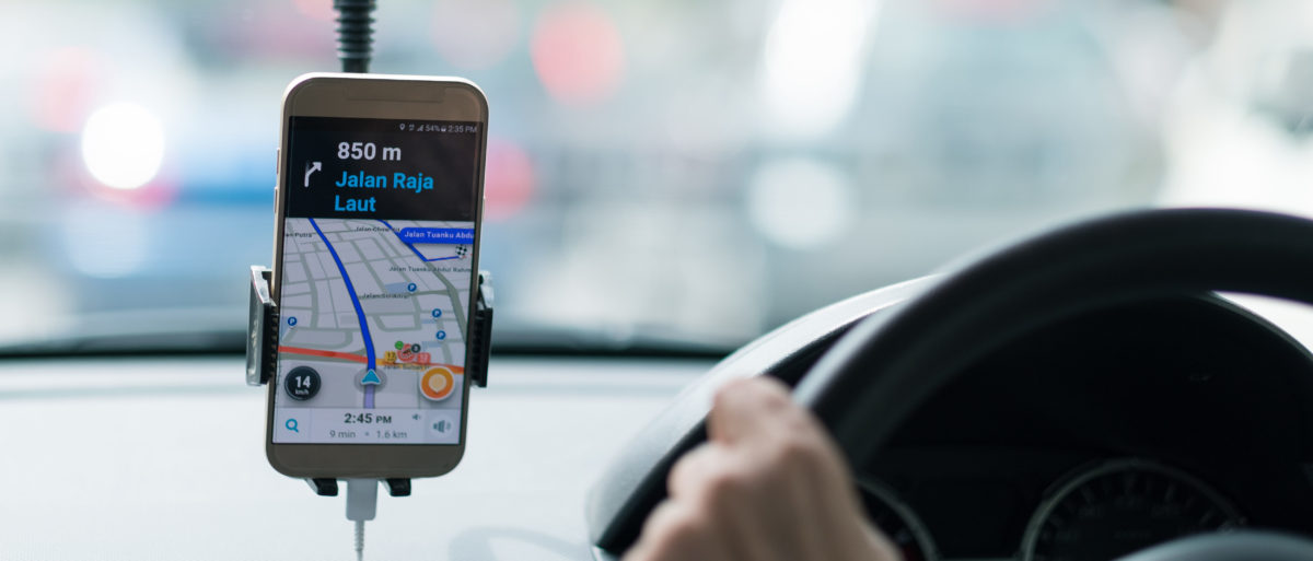 A driver uses his phone to navigate. Shutterstock image via structuresxx
