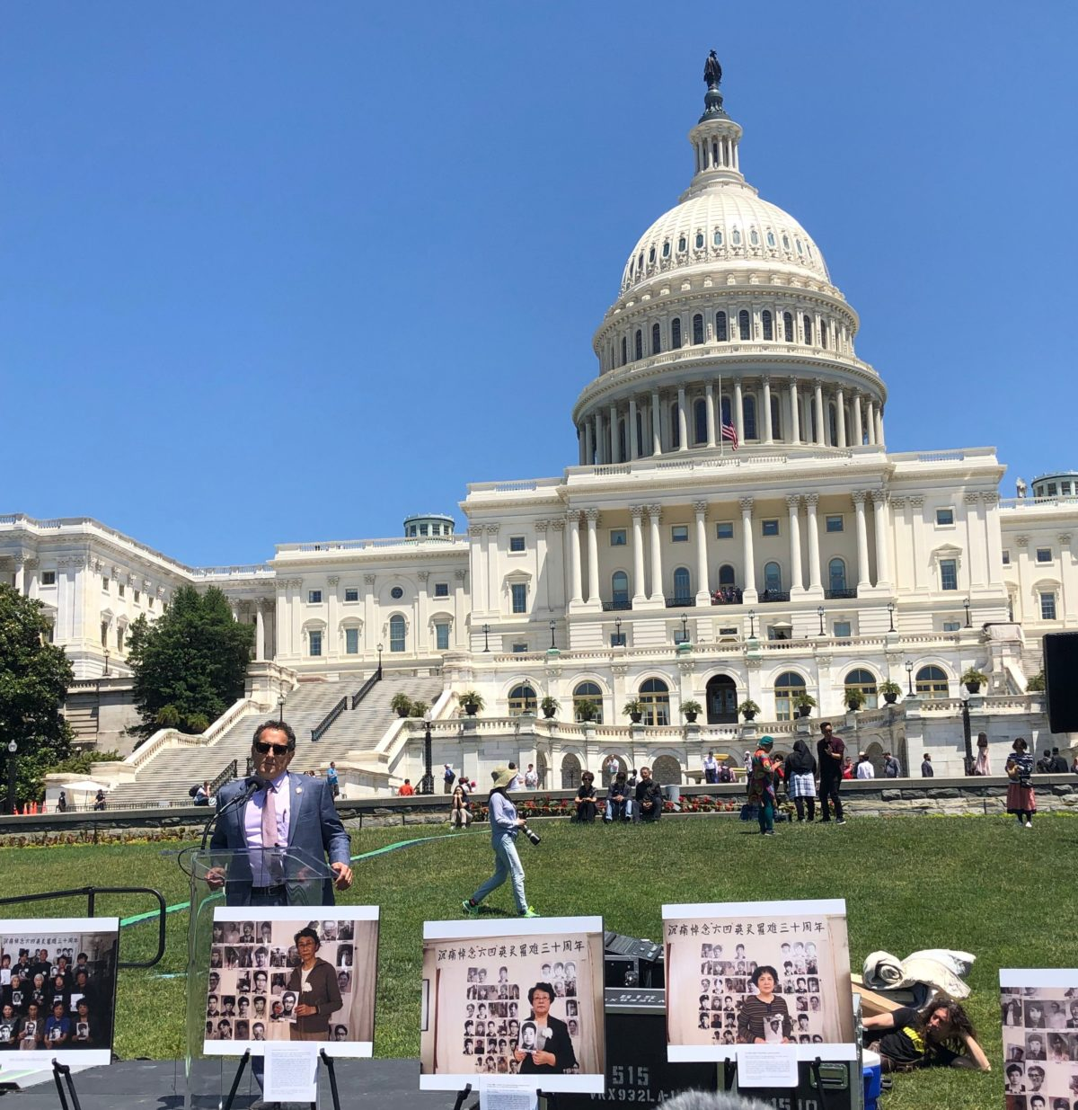 Rep. Andy Levin speaks from behind portraits of relatives holding photos of loved ones killed in Tiananmen Square at a rally commemorating the 30th anniversary of the Massacre in Washington, D.C., on June 4, 2019. Photo by Evie Fordham