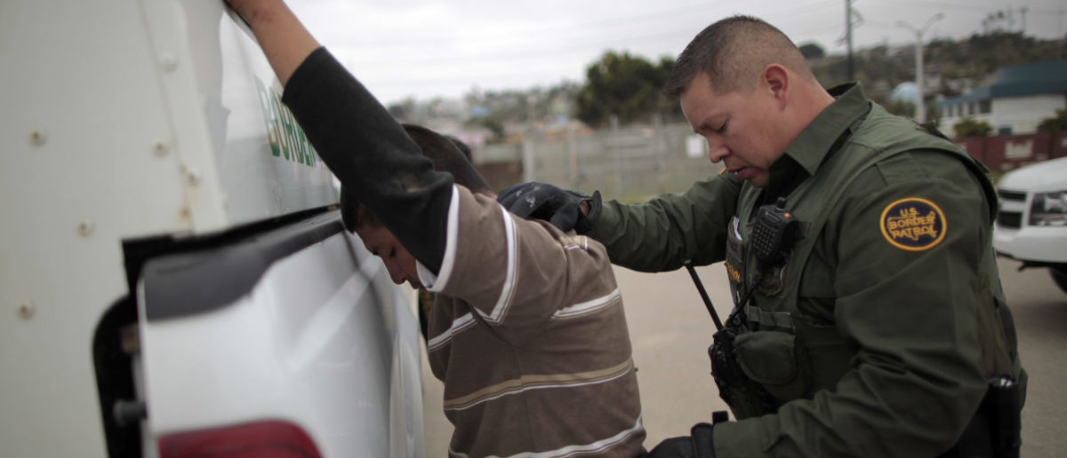 A United States border patrol agent catches an illegal immigrant crossing from Mexico to the U.S. in San Ysidro, California, April 13, 2011. REUTERS/Lucy Nicholson