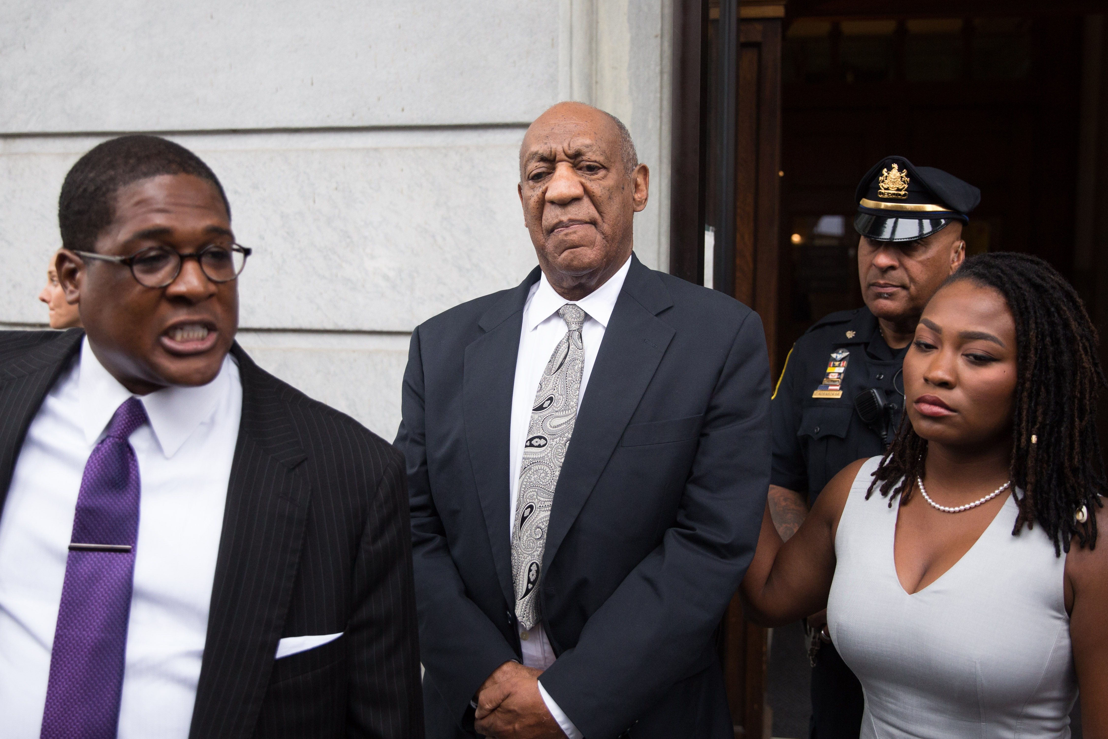 Actor and comedian Bill Cosby looks on as his publicist Andrew Wyatt addresses the media outside the Montgomery County Courthouse on June 17, 2017 in Norristown, Pennsylvania. After 52 hours of deliberation, a mistrial was announced in Cosby's sexual assault trial. (Photo by Kevin Hagen/Getty Images)