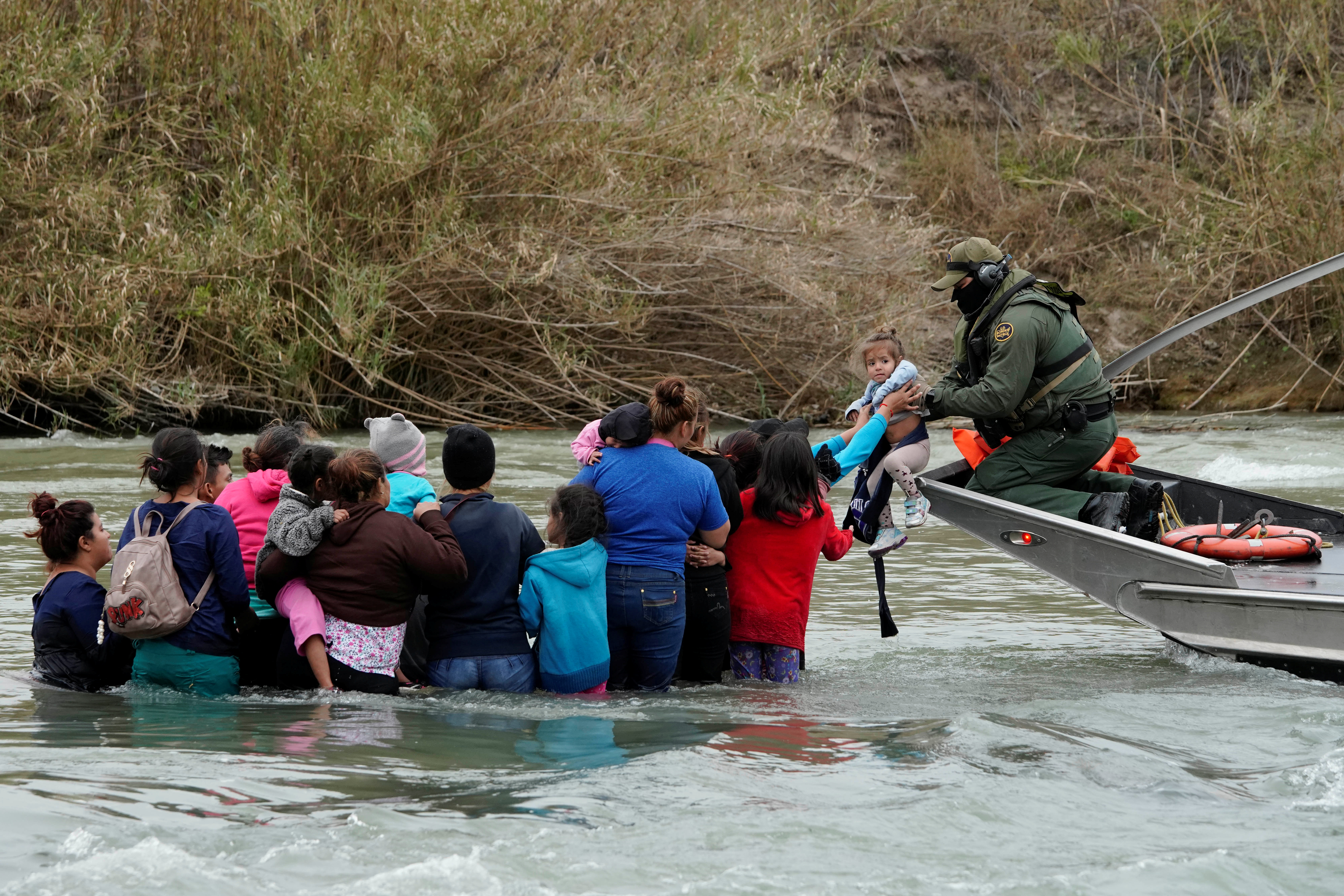 A U.S. border patrol agent rescues migrants crossing the Rio Bravo towards the United States, in Piedras Negras