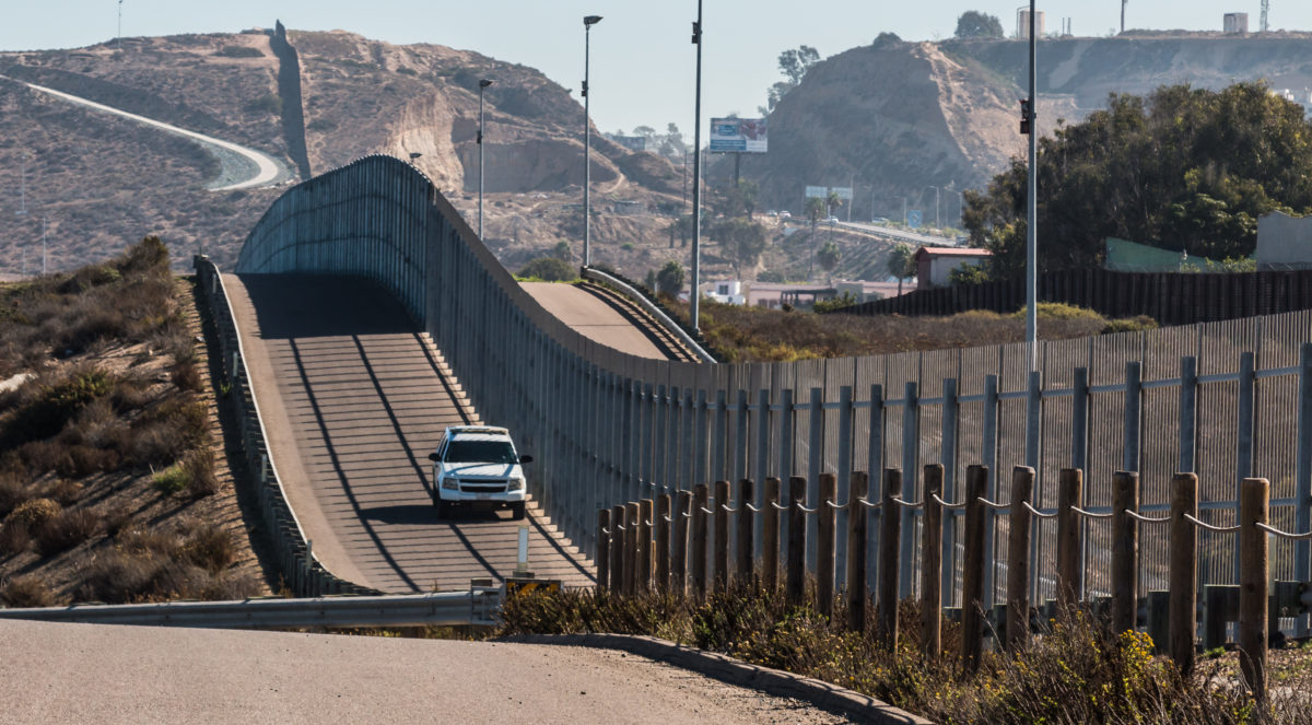 Border Patrol vehicle patrolling along the fence of the international border. Shutterstock