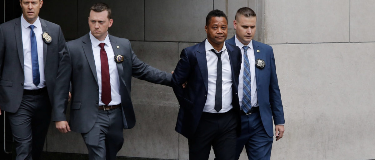 Actor Cuba Gooding Jr. is escorted handcuffed by NYPD officers as he exits the New York City Police Department's (NYPD) Special Victims Division (SVU) in the Harlem neighbourhood of New York, U.S., June 13, 2019. REUTERS/Eduardo Munoz