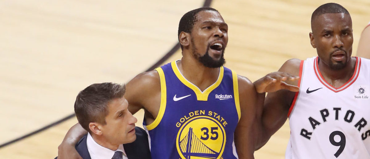 TORONTO, ONTARIO - JUNE 10: Kevin Durant #35 of the Golden State Warriors is assisted off the court after sustaining an injury in the first half against the Toronto Raptors during Game Five of the 2019 NBA Finals at Scotiabank Arena on June 10, 2019 in Toronto, Canada. (Photo by Claus Andersen/Getty Images)