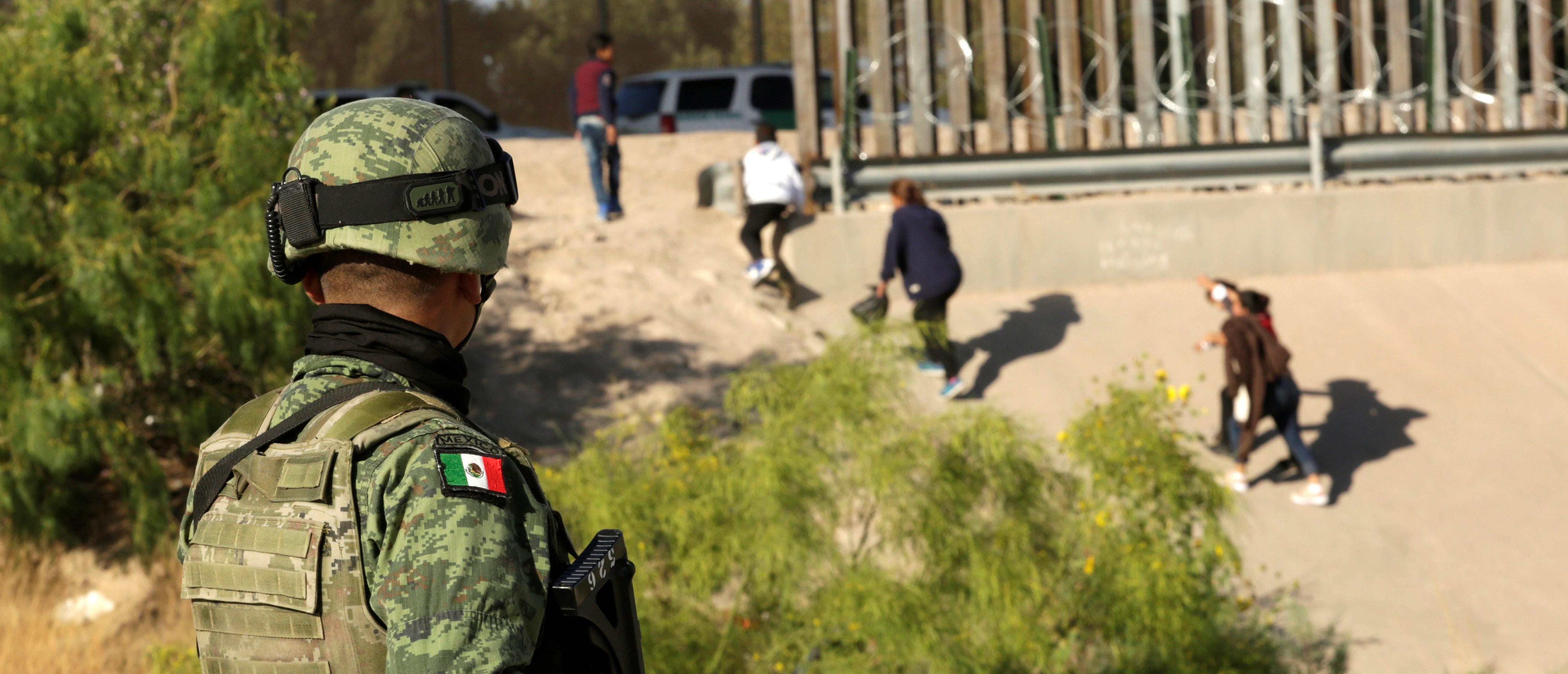 A member of the National Guard looks at migrants that crossed illegally into El Paso, Texas, U.S., from Ciudad Juarez, in Ciudad Juarez, Mexico June 19, 2019. REUTERS/Jose Luis Gonzalez