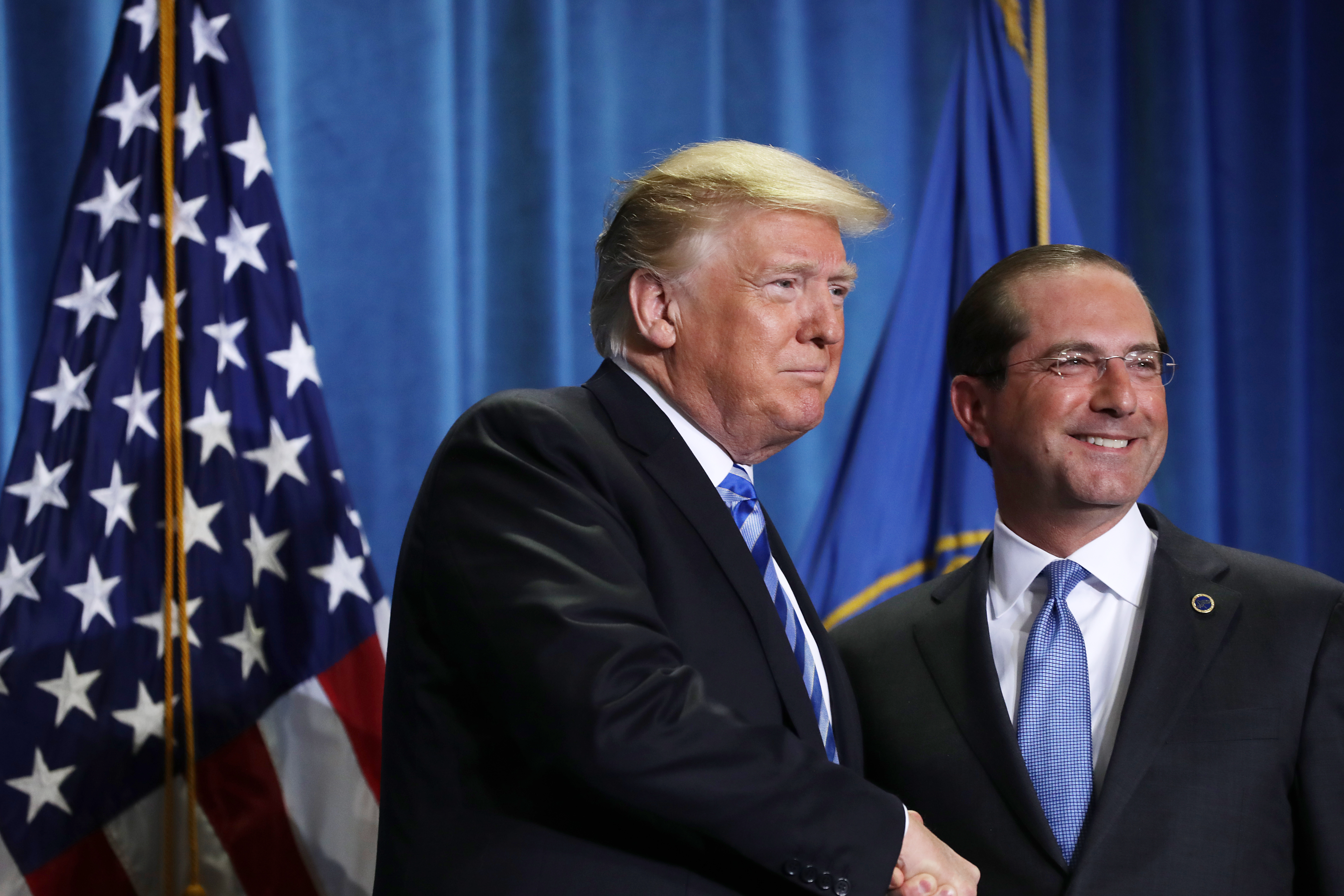 WASHINGTON, DC - OCTOBER 25: AFP OUT U.S. President Donald Trump (L) shakes hands with Health and Human Services Secretary Alex Azar before announcing a plan to overhaul how Medicare pays for certain drugs during a speech at HHS headquarters October 25, 2018 in Washington, DC. Claiming that 'global freeloading' has driven up drug costs, Trump said his plan could save Medicare more than $17 billion over five years, with the cost of some drugs dropping by as much as 30 percent. (Photo by Chip Somodevilla/Getty Images)