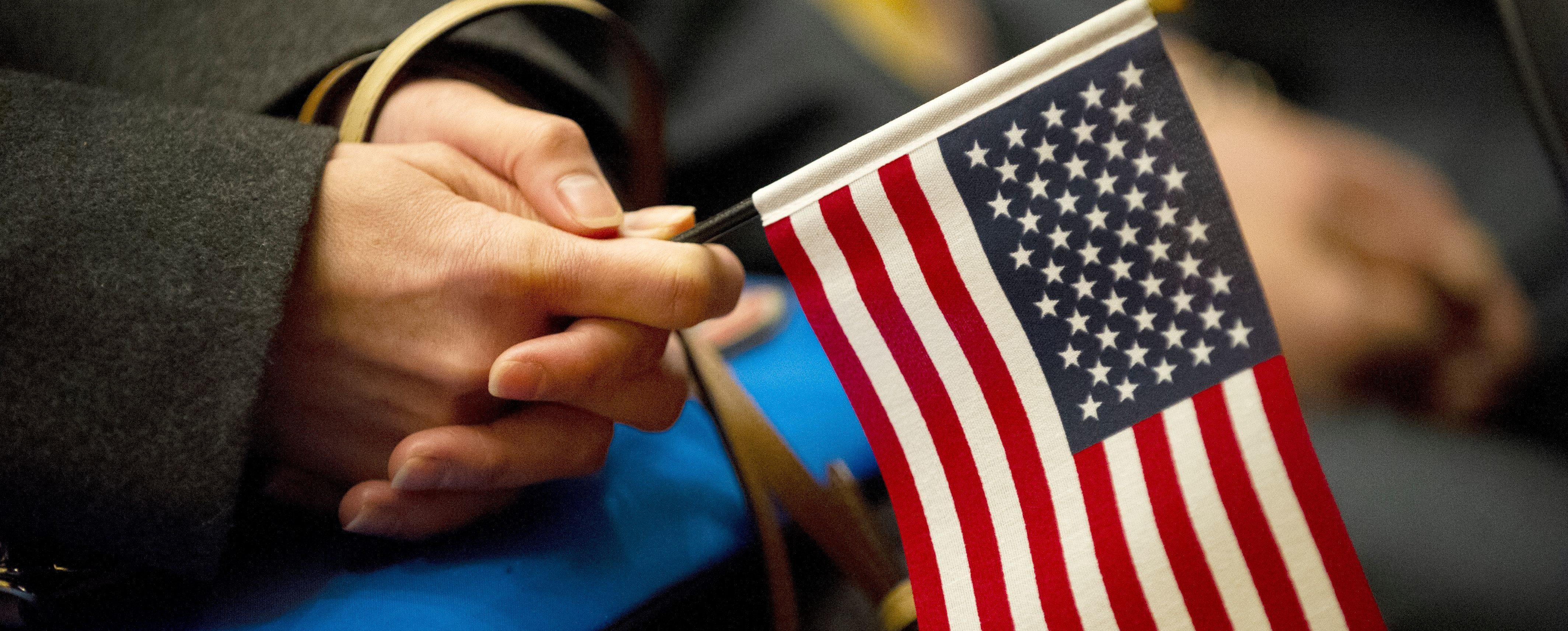 A woman holds a US Flag during a naturalization ceremony at the Lowell Auditorium where 633 immigrants became US citizens on January 22, 2019 in Lowell, Massachusetts. (Photo by Joseph PREZIOSO / AFP) (Photo credit should read JOSEPH PREZIOSO/AFP/Getty Images)