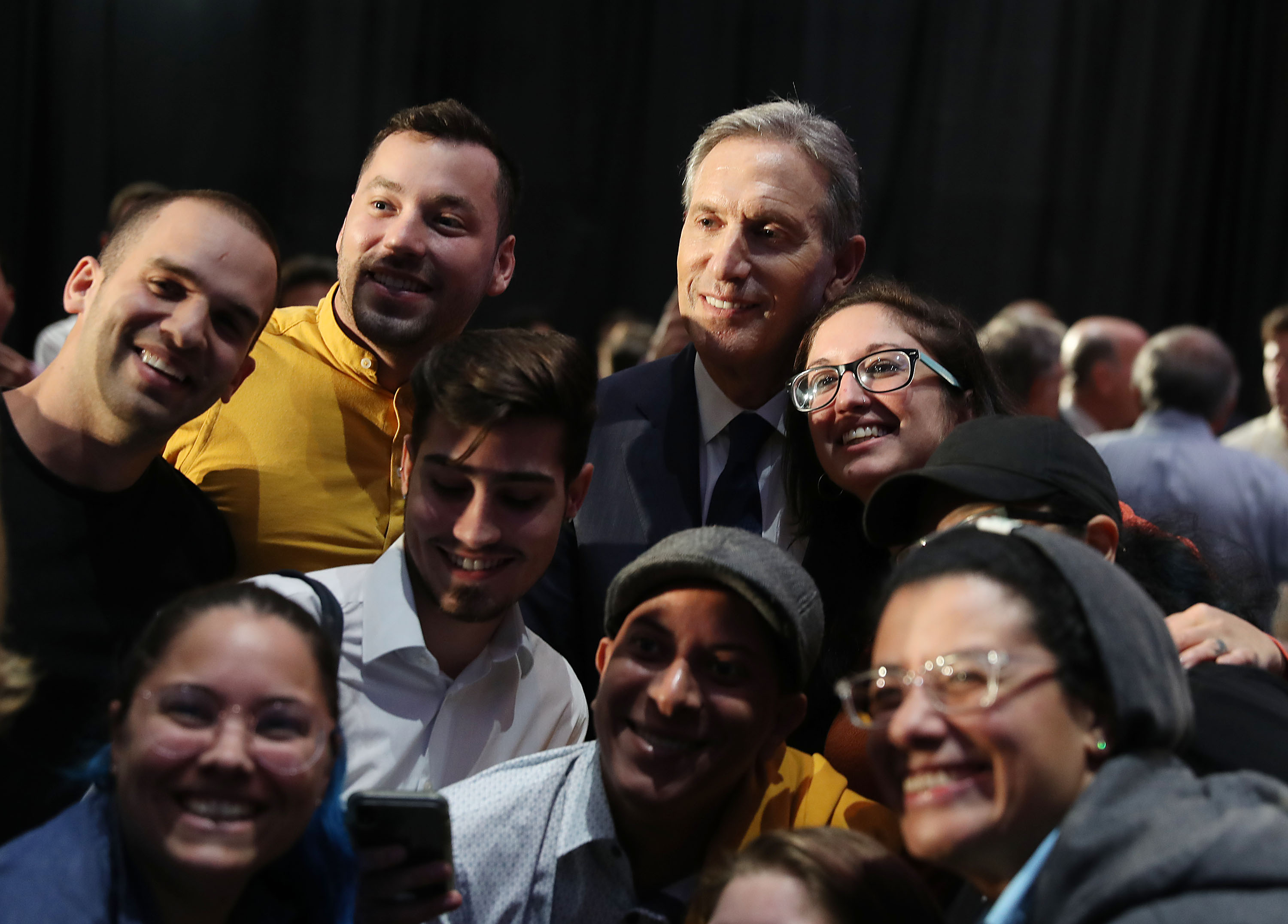 Former Starbucks CEO Howard Schultz poses for a picture with people during a stop at Miami Dade College as he seeks a possible independent presidency run on March 13, 2019 in Miami, Florida. (Photo by Joe Raedle/Getty Images)
