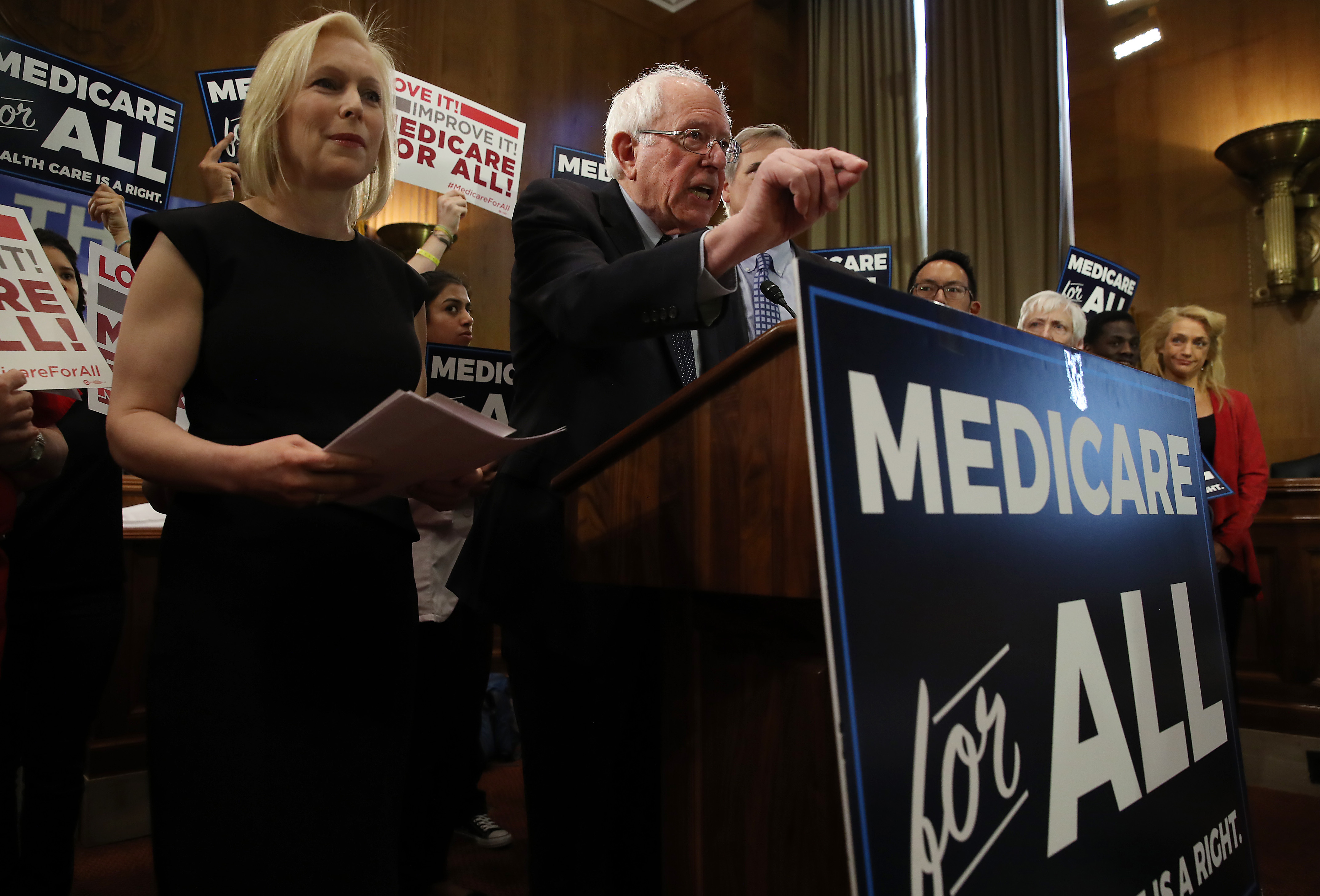 Sen. Kirsten Gillibrand (D-NY) stands next to Sen. Bernie Sanders (I-VT) while he speaks while introducing health care legislation during a news conference on Capitol Hill, on April 9, 2019. (Photo by Mark Wilson/Getty Images)
