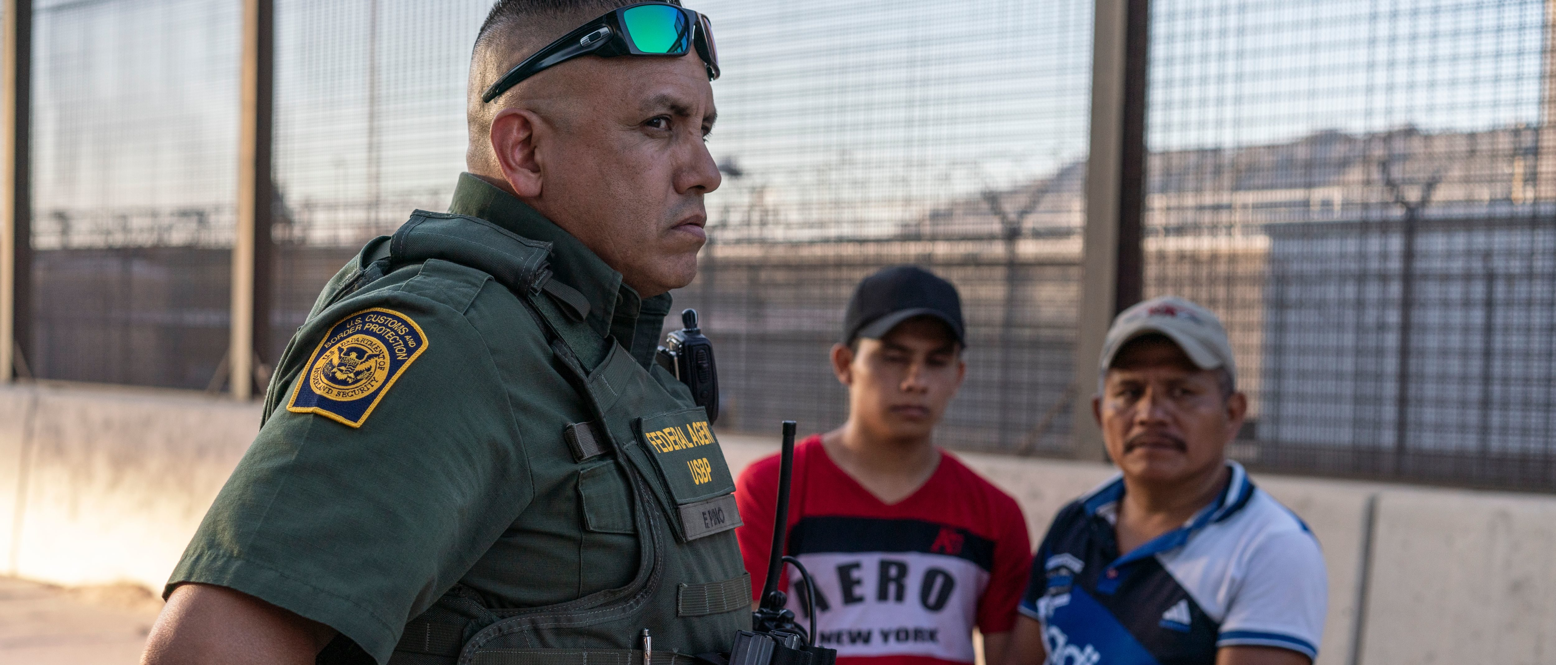 "Border Patrol agent Frank Pino (L) is pictured with two migrants who presented themselves to the Border Patrol in El Paso, Texas on May 16, 2019. - ""It's heart breaking, you know, I'm a father. I have two children. These guys out here, they are here with their kids,"" Pino said, ""I kind of put myself in their position, and you know, would I do the same thing they're doing? Escaping violence or fleeing their countries, it's a hard decision, but I took an oath as a Border Patrol agent, my main priority is protecting this border, protecting this fence, and making sure that we identify for the security of my community where I live in El Paso, Texas. That's important to me."" About 1,100 migrants from Central America and other countries are crossing into the El Paso border sector each day. Pino, public information officer for the Border Patrol, says that Border Patrol resources and personel are being stretched by the ongoing migrant crisis, and that the real targets of the Border Patrol are slipping through the cracks. (Photo by Paul Ratje / AFP) (Photo credit should read PAUL RATJE/AFP/Getty Images)"