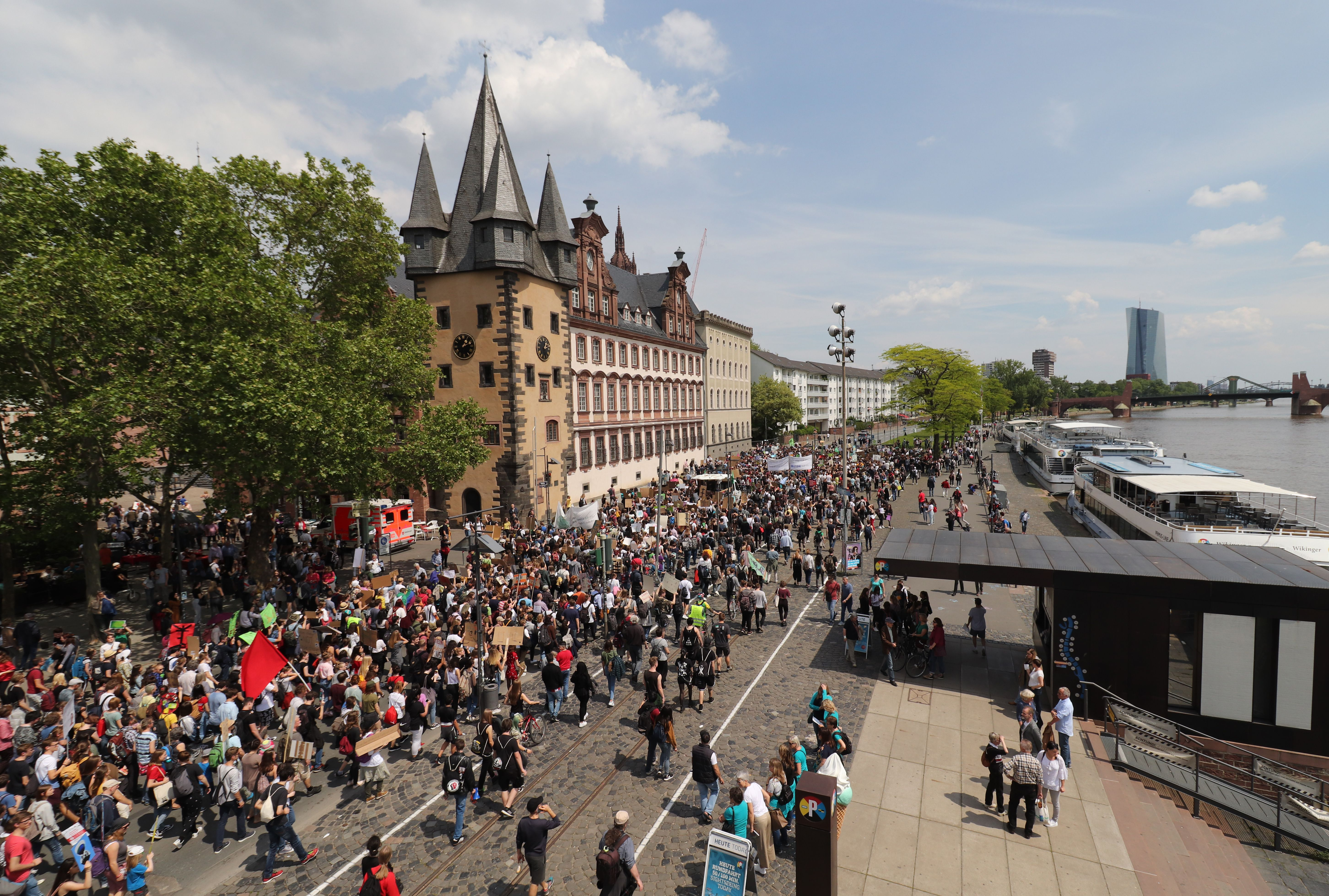 "The headquarters of the European Central Bank (ECB) is pictured in the background as people take part in the ""Global Strike For Future"" demonstration in Frankfurt am Main, western Germany on May 24, 2019, a global day of student protests aiming to spark world leaders into action on climate change. (YANN SCHREIBER/AFP/Getty Images)"