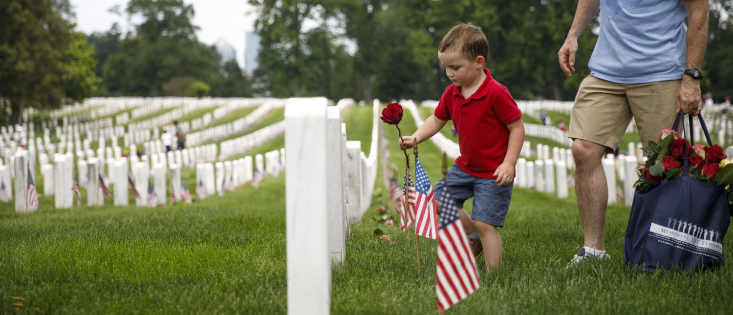 ARLINGTON, VA - MAY 26: Matthew Murphy, 4, places a rose on a tombstone beside his father, Kevin Murphy, of Springfield, Virginia, during a volunteer event at Arlington National Cemetery ahead of Memorial Day on May 26, 2019 in Arlington, Virginia. Memorial Day marks the unofficial start of the summer season and its purpose is to honor those who died while serving in the U.S. military. (Photo by Tom Brenner/Getty Images)