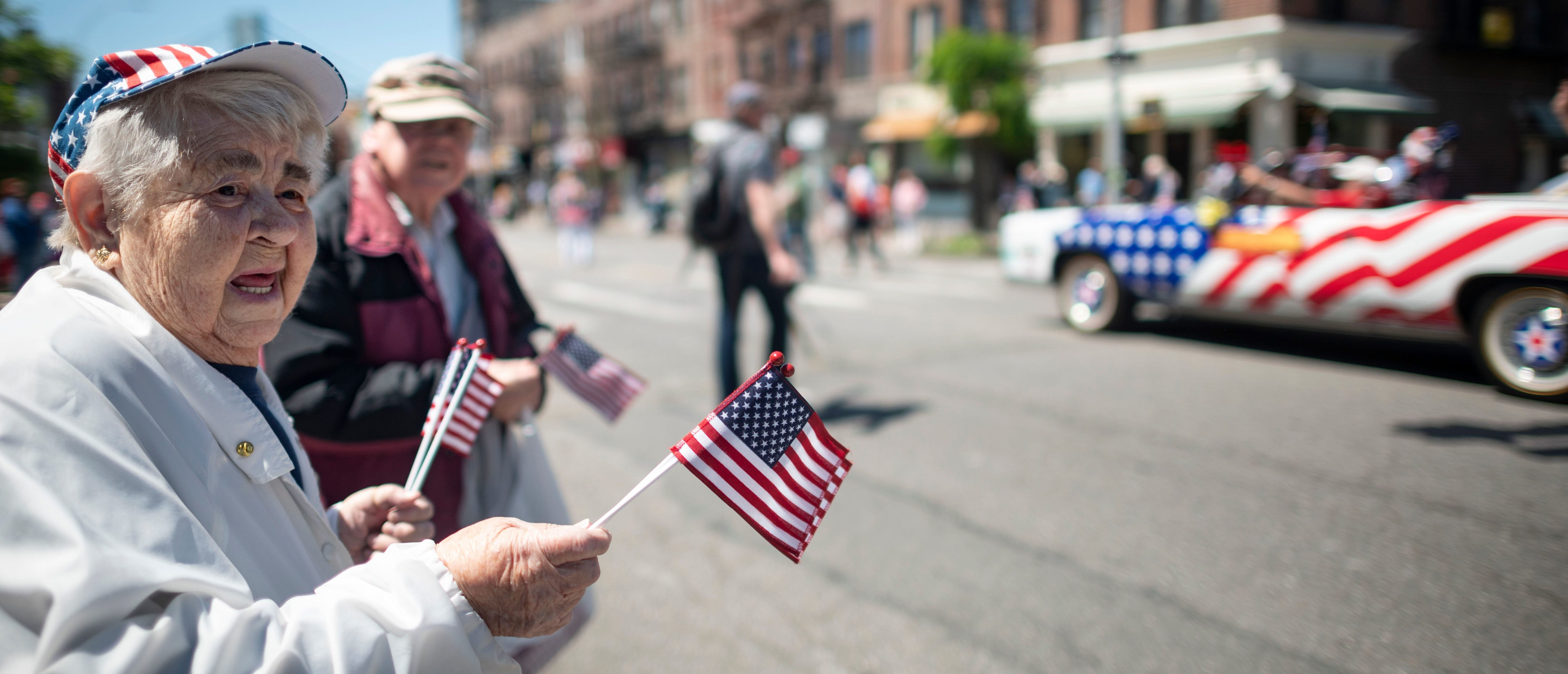 An elderly woman waves American flags to veterans as they march on the street May 27, 2019 during the 152nd Memorial Day Parade in the New York City borough of Brooklyn. (JOHANNES EISELE/AFP/Getty Images)
