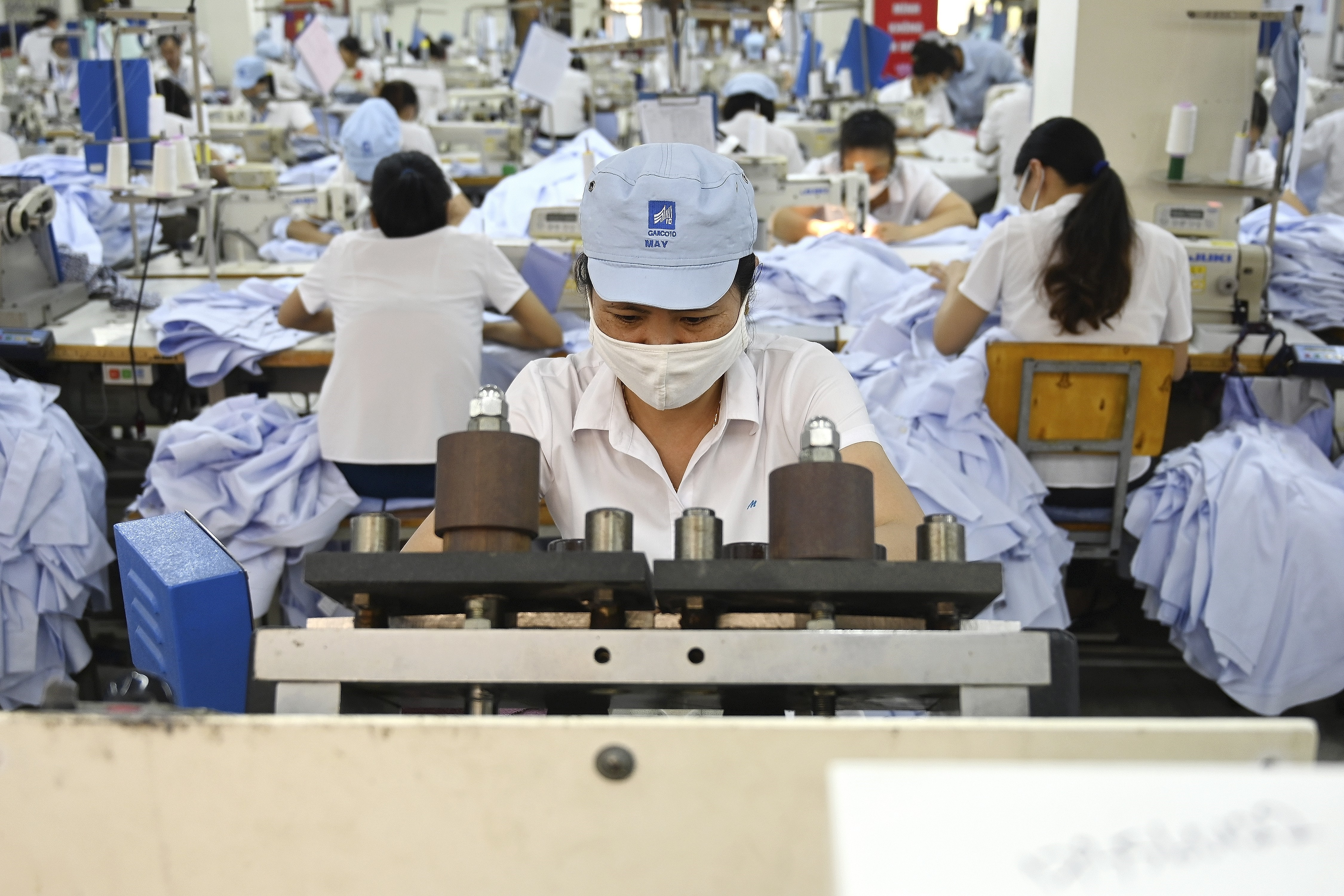 This photo shows garment stitching apparel in a factory in Hanoi. Countries across Asia are hoping the US tariff squeeze on China will presage a permanent shift in manufacturing patterns as big name brands dodge the trade war in cheaper locations to make their goods. (MANAN VATSYAYANA/AFP/Getty Images)