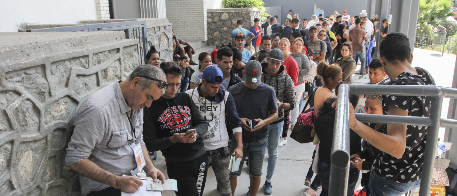 "Cuban asylum seekers queue for a turn for an asylum appointment with US authorities in Ciudad Juarez, Chihuahua state, Mexico, on May 31, 2019. - Washington will impose a five percent tariff on all goods from Mexico starting on June 10, a measure that will last until ""illegal migrants"" stop coming through the country into the US, President Donald Trump said Thursday. (Photo by HERIKA MARTINEZ/AFP/Getty Images)"