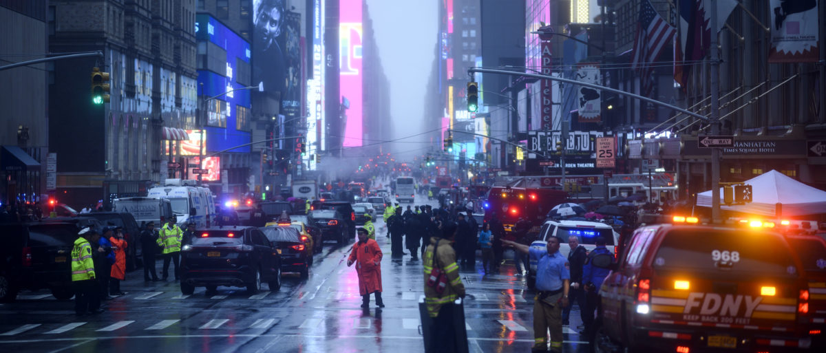 Policemen stand near emergency services vehicles after a helicopter crash-landed on top of a building in midtown Manhattan in New York on June 10, 2019. (JOHANNES EISELE/AFP/Getty Images)