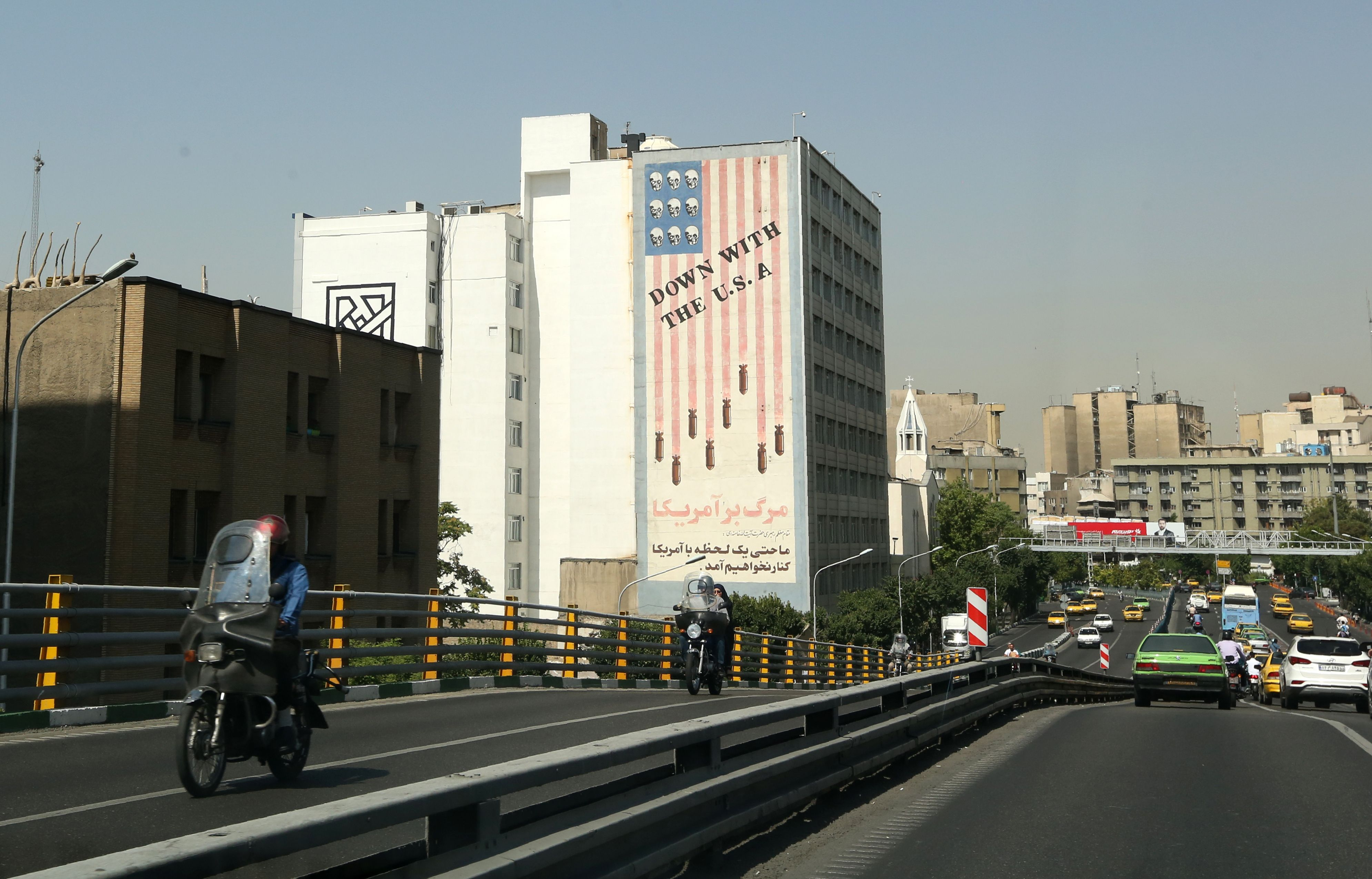 Cars drive past mural painting along the wall of a building in the Iranian capital Tehran on June 22, 2019. (Photo by ATTA KENARE / AFP) / The erroneous mention[s] appearing in the metadata of this photo by ATTA KENARE has been modified in AFP systems in the following manner: [wall of a building] instead of [wall of the former US embassy]. Please immediately remove the erroneous mention[s] from all your online services and delete it (them) from your servers. If you have been authorized by AFP to distribute it (them) to third parties, please ensure that the same actions are carried out by them. Failure to promptly comply with these instructions will entail liability on your part for any continued or post notification usage. Therefore we thank you very much for all your attention and prompt action. We are sorry for the inconvenience this notification may cause and remain at your disposal for any further information you may require.(ATTA KENARE/AFP/Getty Images)