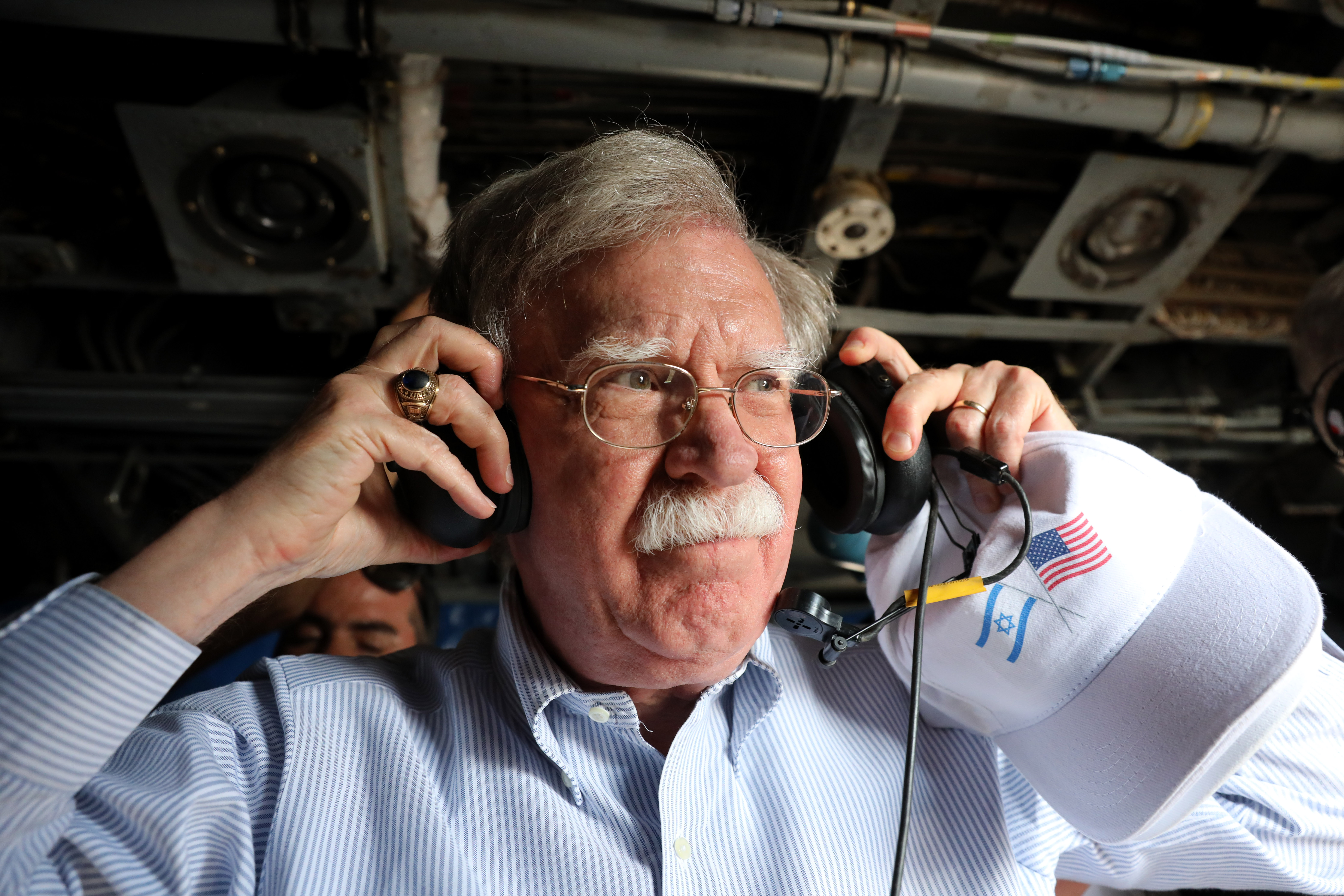 US National Security Advisor John Bolton grabs ear protectors during a flight over the Jordan Valley between the Israeli city of Beit Shean and the West Bank Palestinian city of Jericho on June 23, 2019. (Photo by ABIR SULTAN / POOL / AFP) (Photo credit should read ABIR SULTAN/AFP/Getty Images)