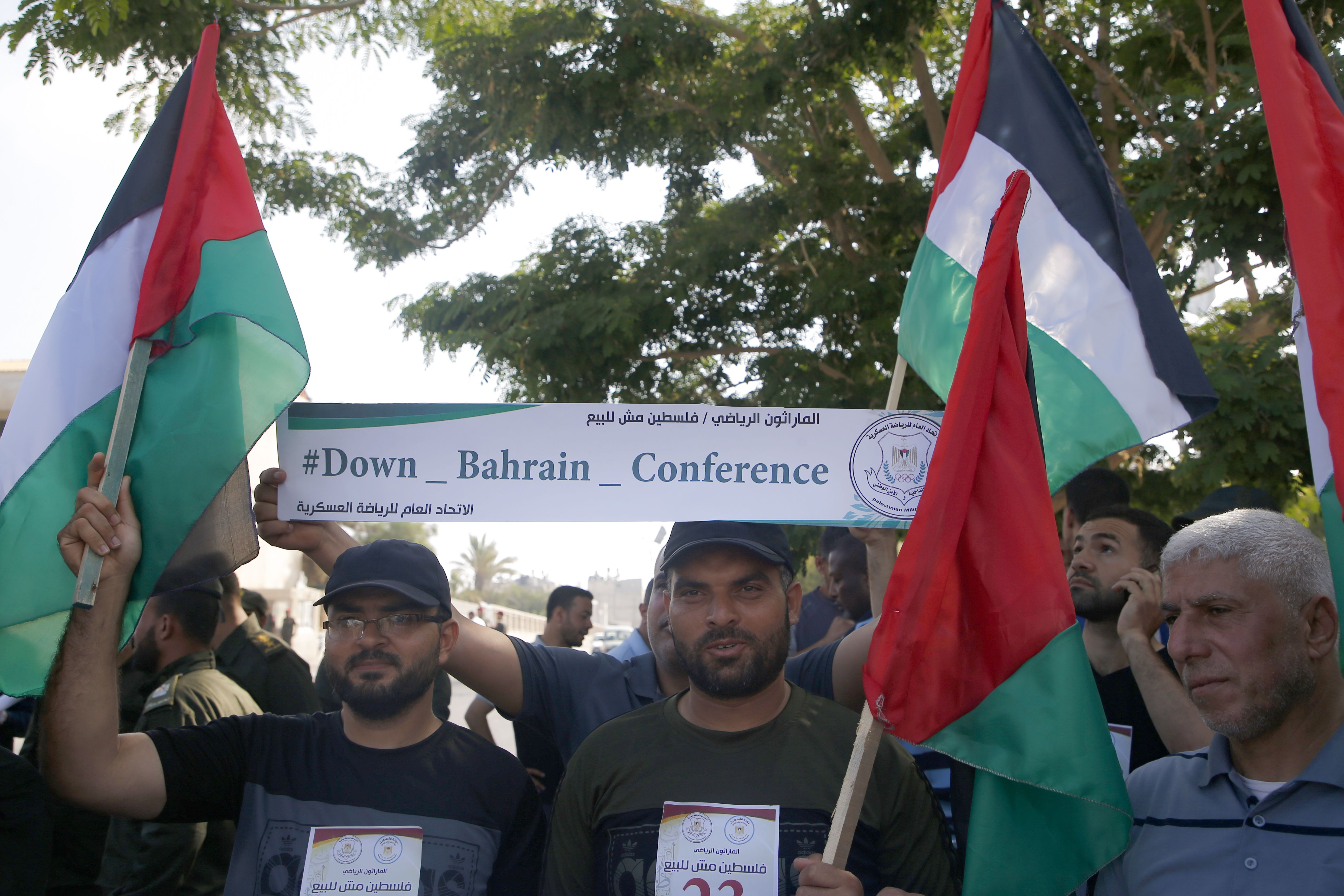 Paletinians wave national flags and hold a banner denouncing the US-led Peace to Prosperity conference that opens tomorrow in Bahrain, in Gaza City on June 24, 2019. - The peace conference on the Palestinian economy could present Washington with a new opportunity to push Gulf allies and Israel closer together as tensions with common foe Iran rise. (MOHAMMED ABED/AFP/Getty Images)