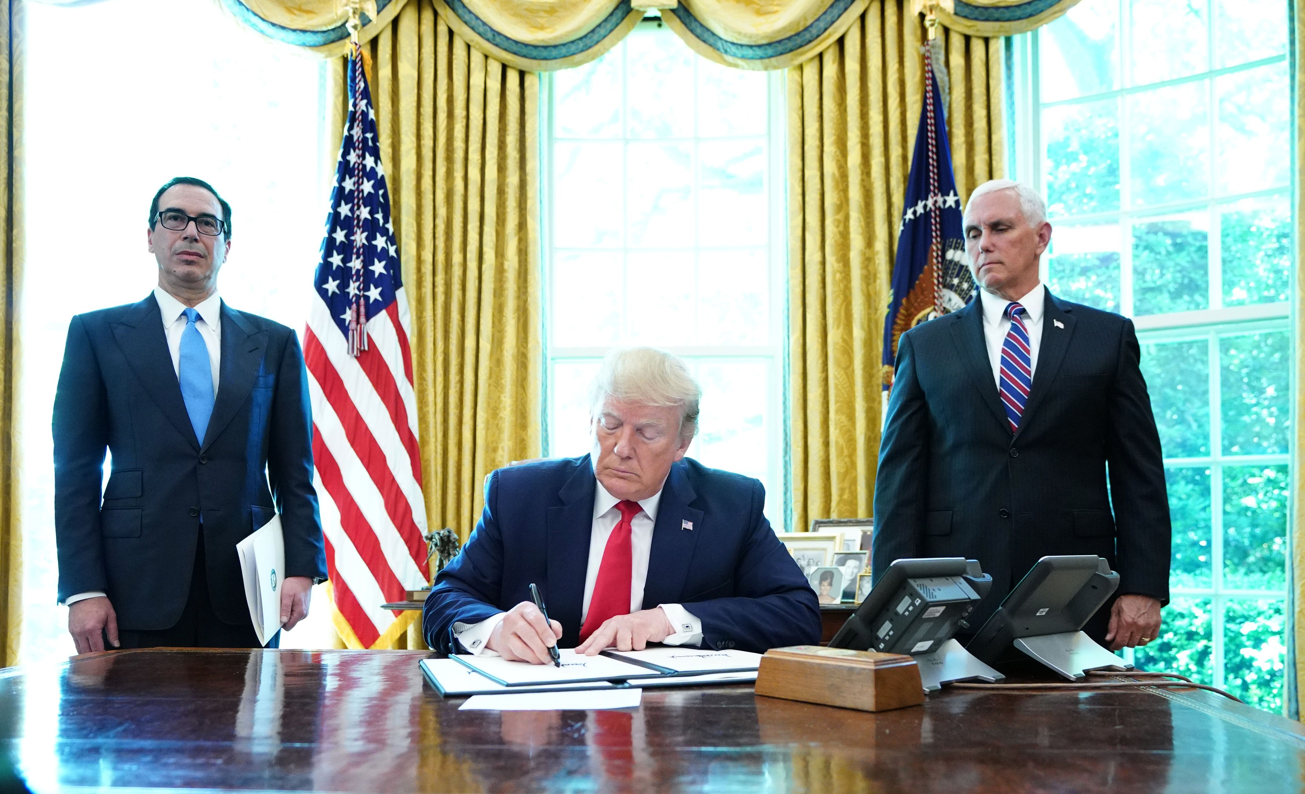 US President Donald Trump signs with US Vice President Mike Pence and US Secretary of Treasury Steven Mnuchin at the White House on June 24, 2019, 'hard-hitting sanctions' on Iran's supreme leader. (MANDEL NGAN/AFP/Getty Images)