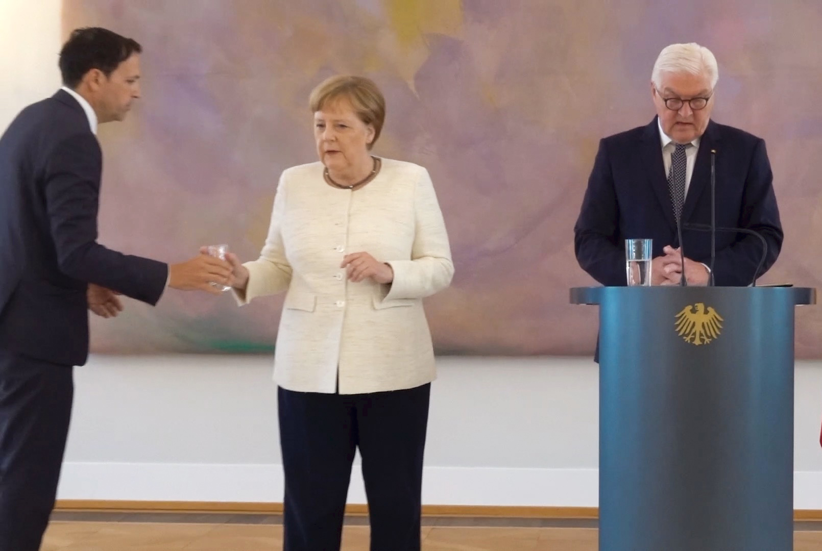 German Chancellor Angela Merkel refuses a glass of water offered to her as she attends a ceremony where the country's new Justice Minister was given her certificate of appointment by German President Frank-Walter Steinmeier (R) at the presidential Bellevue Palace in Berlin on June 27, 2019. (KAY NIETFELD/AFP/Getty Images)