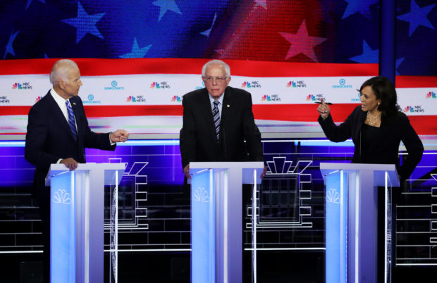 MIAMI, FLORIDA - JUNE 27: Sen. Kamala Harris (R) (D-CA) and former Vice President Joe Biden (L) speak as Sen. Bernie Sanders (I-VT) looks on during the second night of the first Democratic presidential debate on June 27, 2019 in Miami, Florida. (Photo by Drew Angerer/Getty Images)
