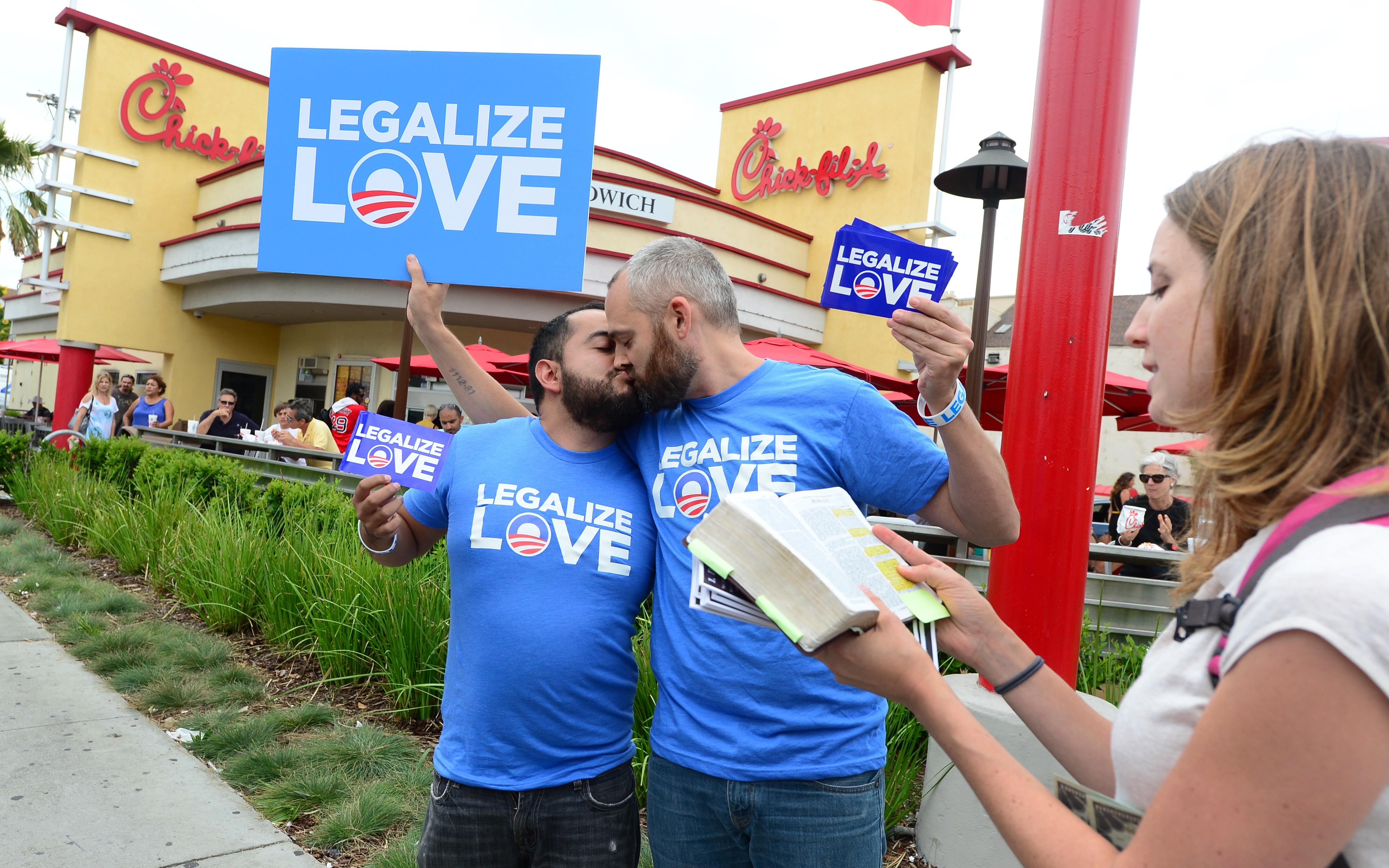 "Eduardo Cisneros (L) and Luke Montgomery (C) kiss in front of a Chick-fil-A fast food restaurant in Hollywood as Christian activist Alicia Daberkow (R) reads passages from the Bible on August 3, 2012 in Hollywood, California. Gays and lesbians puckered up in protest Friday, staging ""kiss-ins"" outside Chick-fil-A outlets across the United States over the fast food chain's opposition to same-sex marriage. (FREDERIC J. BROWN/AFP/GettyImages)"