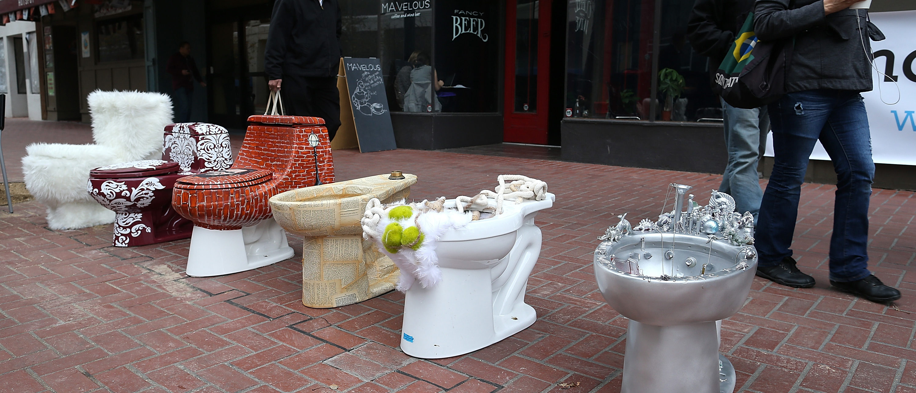 """SAN FRANCISCO, CA - NOVEMBER 21: Decorated toilets are displayed as part of a public art installation titled """"C'mon, give a shit"""" to mark World Toilet Day and to bring attention to a project to convert retired MUNI buses into mobile showers for the homeless on November 21, 2013 in San Francisco, California. Lava Mae founder Doniece Sandoval coordinated the public art installation of decorated toilets to raise awareness about the millions of people around the world who do not have access to clean and private toilets. The installation also promotes the nonprofit Lava Mae's project to convert old San Francisco municipal buses into mobile showers for homeless people in the city. (Photo by Justin Sullivan/Getty Images)"""