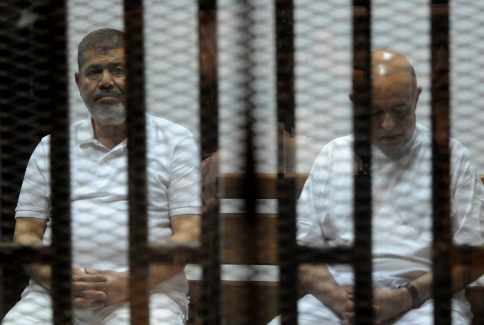 Egypt's deposed Islamist president Mohamed Morsi (L) and former presidential chief of staff Rafaa el-Tahtawi, sit inside the defendants cage during his trial at the police academy in Cairo on October 14, 2014. (STR/AFP/Getty Images)