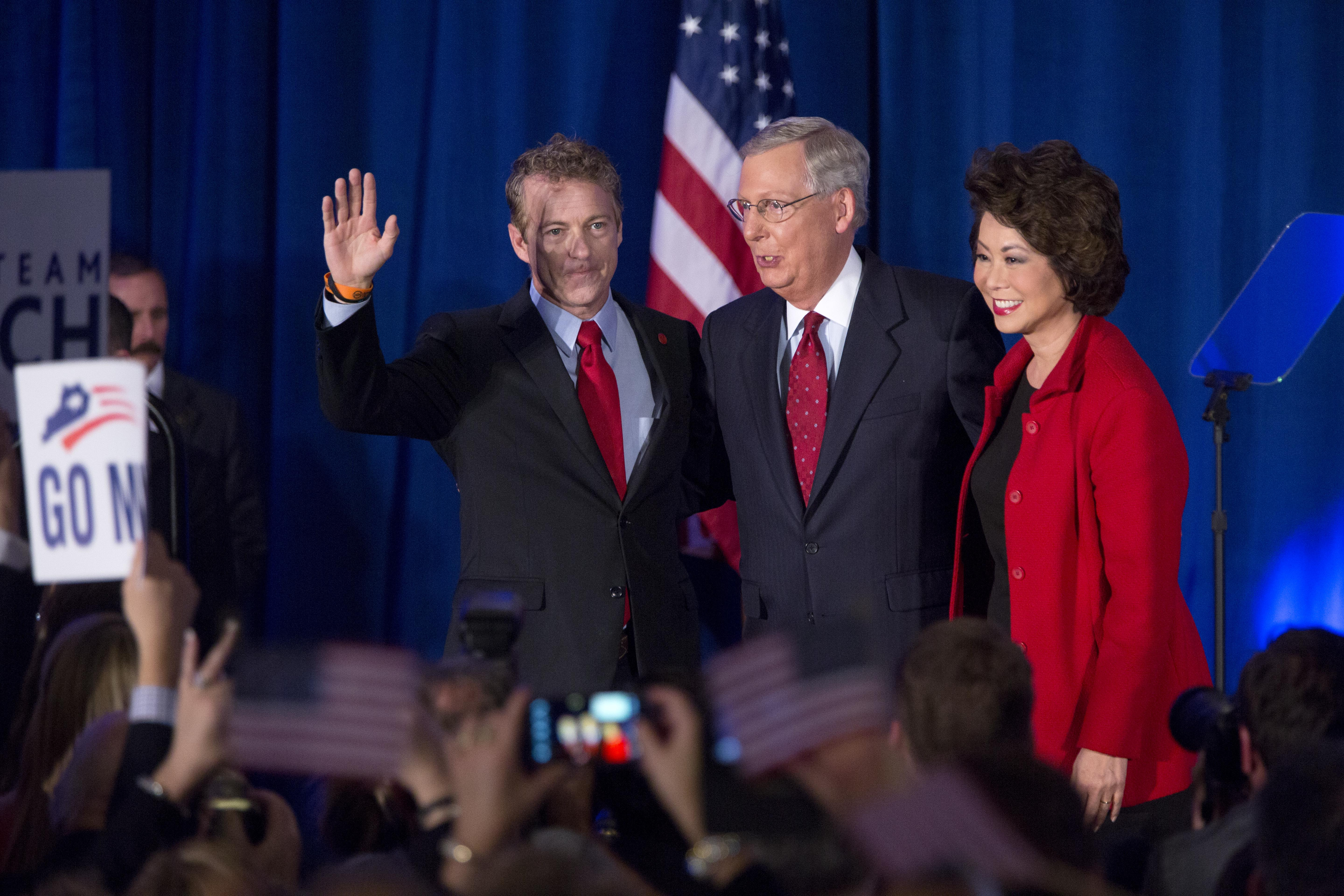 U.S. Sen. Mitch McConnell celebrates with his wife Elaine Chao and U.S. Sen. Rand Paul at his election night event November 4, 2014 in Louisville, Kentucky. (Photo by Aaron P. Bernstein/Getty Images)