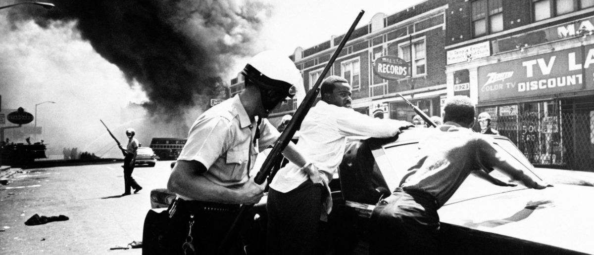 A policeman searches black suspects in a Detroit street on July 25, 1967 as buildings are burning during riots that erupted in Detroit following a police operation. AFP/Getty Images