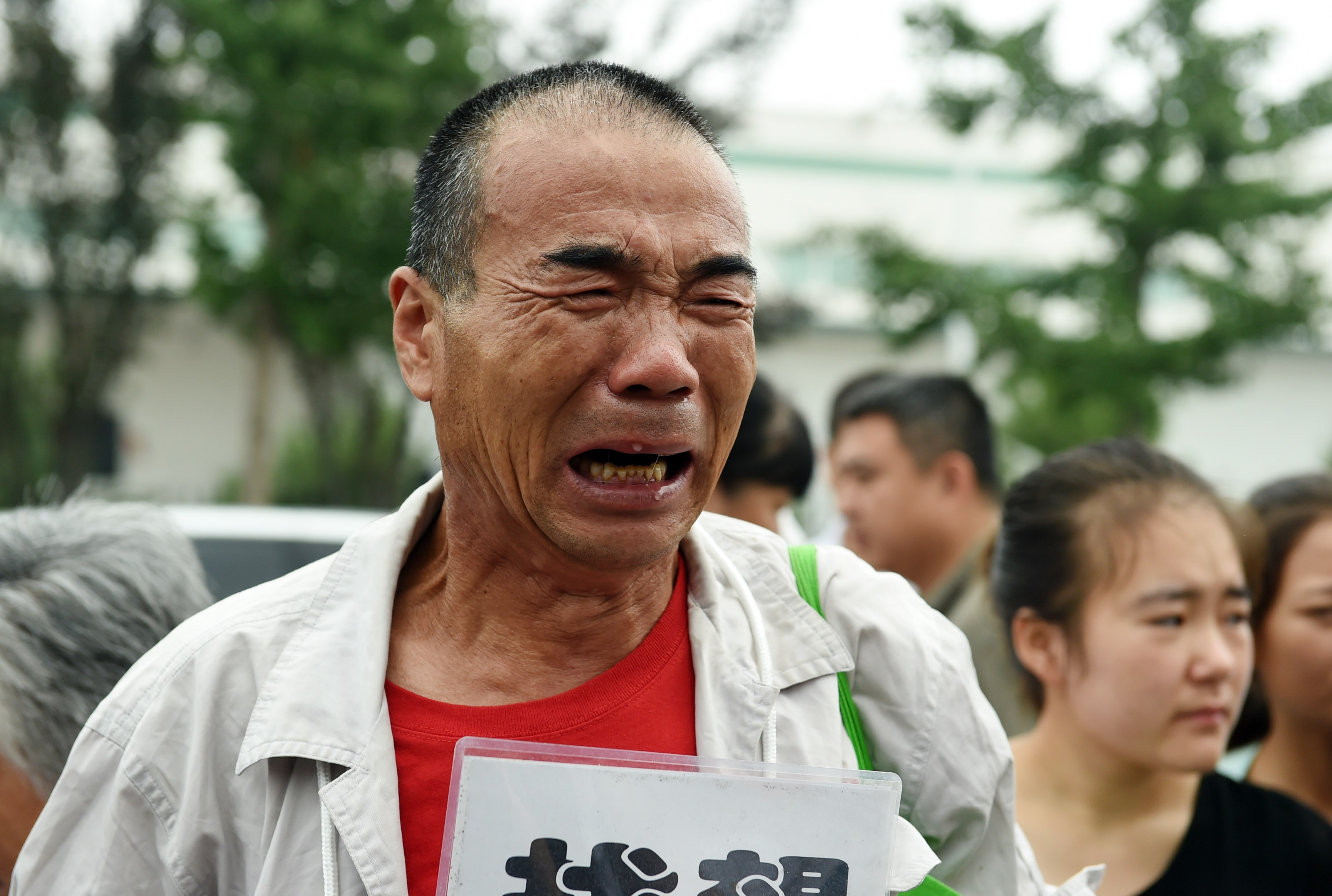 A relative of a passenger on missing Malaysia Airlines MH370 cries while waiting for an expected meeting with Malaysian officials, outside an office on the outskirts of Beijing on August 7, 2015. (GREG BAKER/AFP/Getty Images)