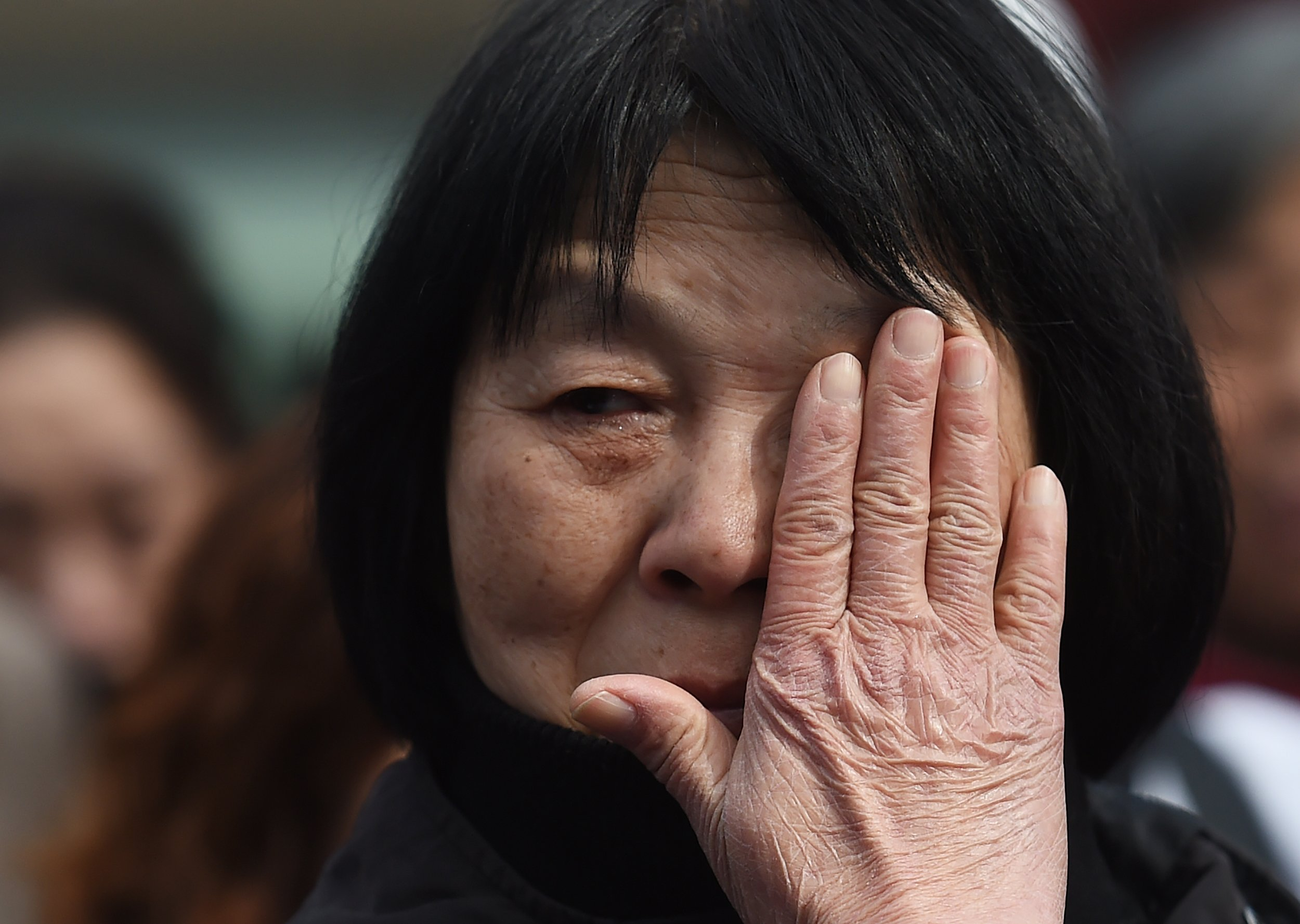 Dai Shuqin, a relative of passengers missing on Malaysia Airlines MH370, wipes her tears during a gathering of relatives outside the Lama Temple in Beijing on March 8, 2016 (GREG BAKER/AFP/Getty Images)
