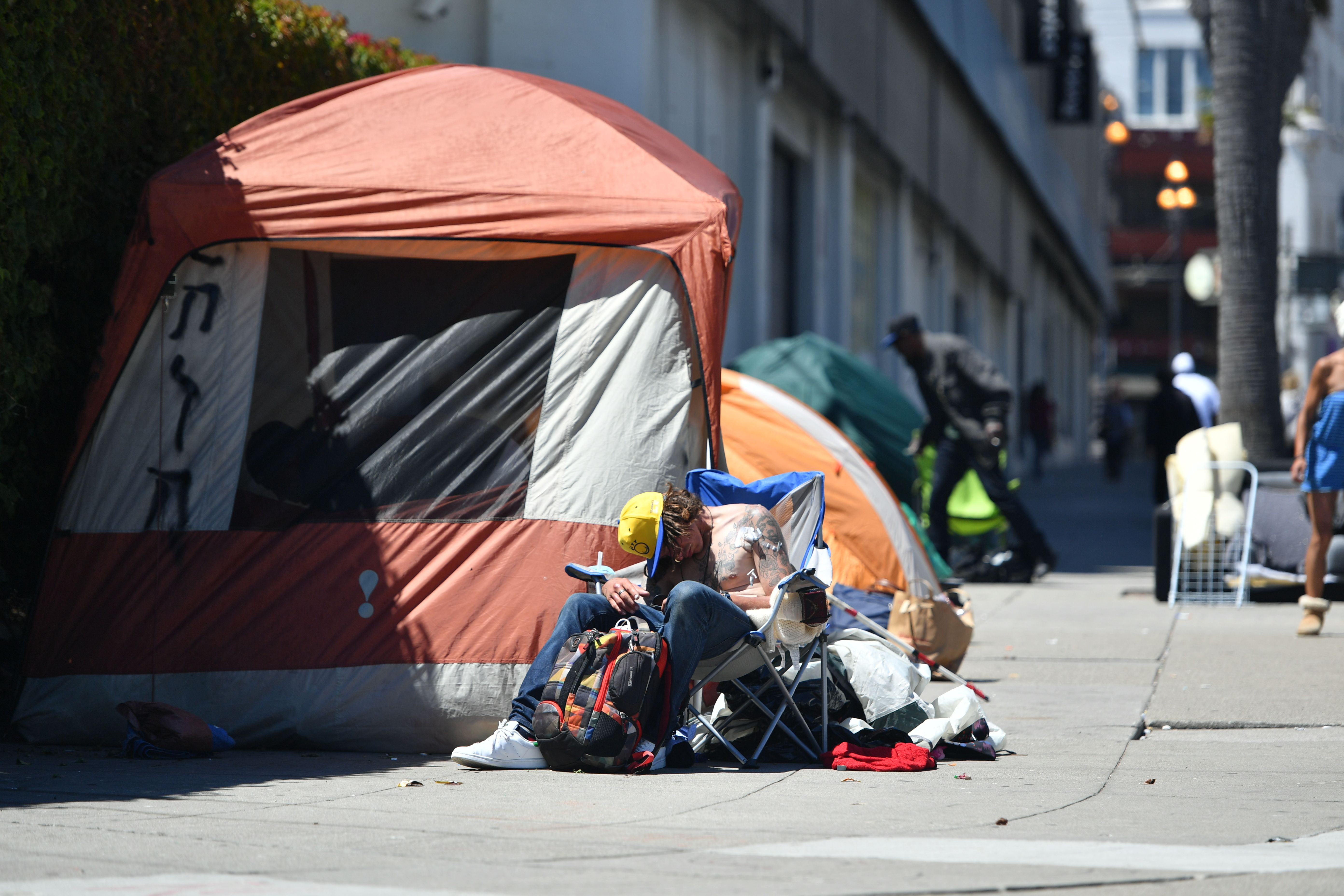 A homeless man sleeps in front of his tent along Van Ness Avenue in downtown San Francisco, California on June, 27, 2016. Homelessness is on the rise in the city irking residents and bringing the problem under a spotlight. (JOSH EDELSON/AFP/Getty Images)