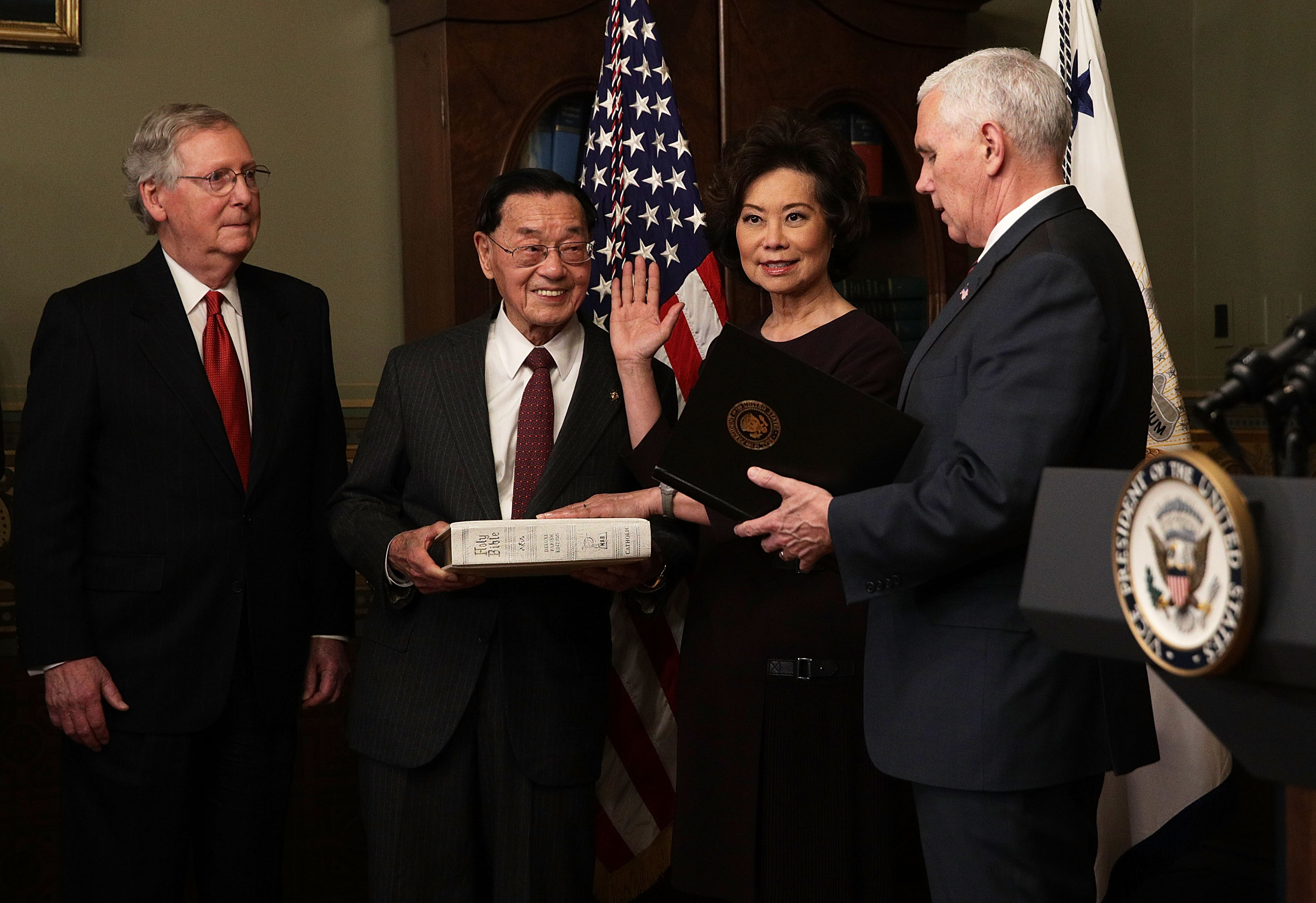 Elaine Chao (3rd L) is sworn in by U.S. Vice President Mike Pence (R) as her father James Chao (2nd L) and her husband Senate Majority Leader Sen. Mitch McConnell (L) look on during a ceremony at the Vice President's ceremonial office at Eisenhower Executive Office Building January 31, 2017 in Washington, DC. (Photo by Alex Wong/Getty Images)