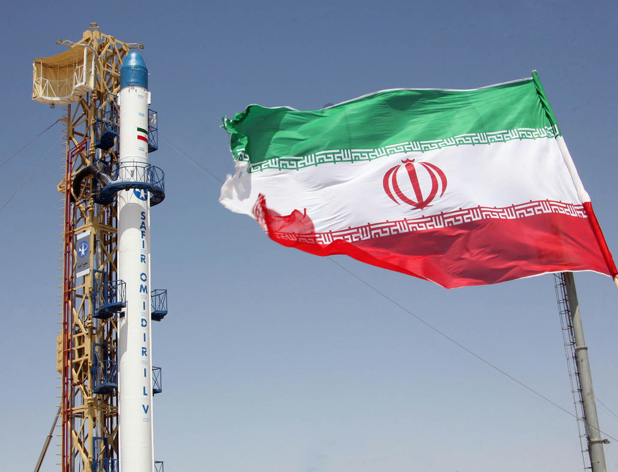 An Iranian flag fluttering in front of Iran's Safir Omid rocket (VAHIDREZA ALAI/AFP/Getty Images)