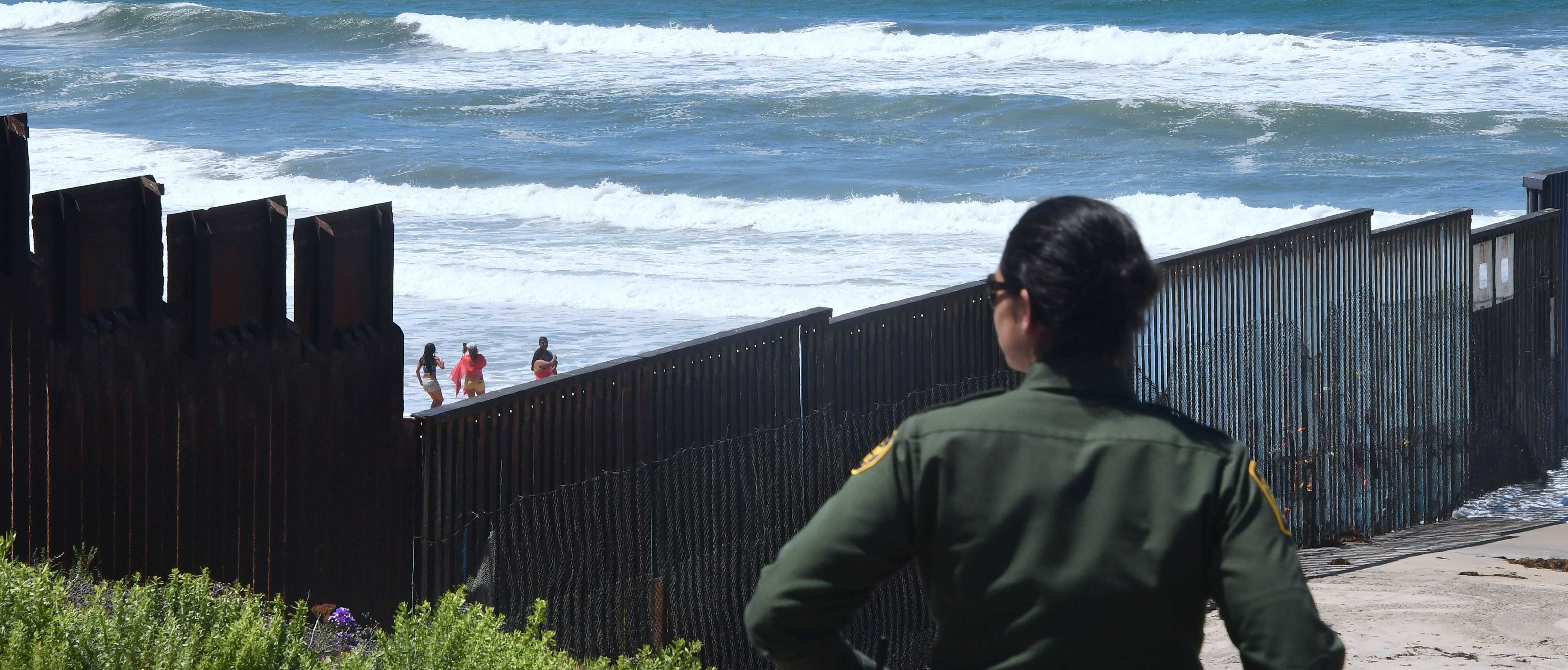 TOPSHOT - A US Customs and Border Protection agent watches from near the end of the border structure which runs into the Pacific Ocean in San Diego, California as people visit the beach in La Playa, Mexico on April 17, 2018 a day after California rejected plans by the federal government for National Guard troops on the border. (Photo by FREDERIC J. BROWN / AFP) (Photo credit should read FREDERIC J. BROWN/AFP/Getty Images)
