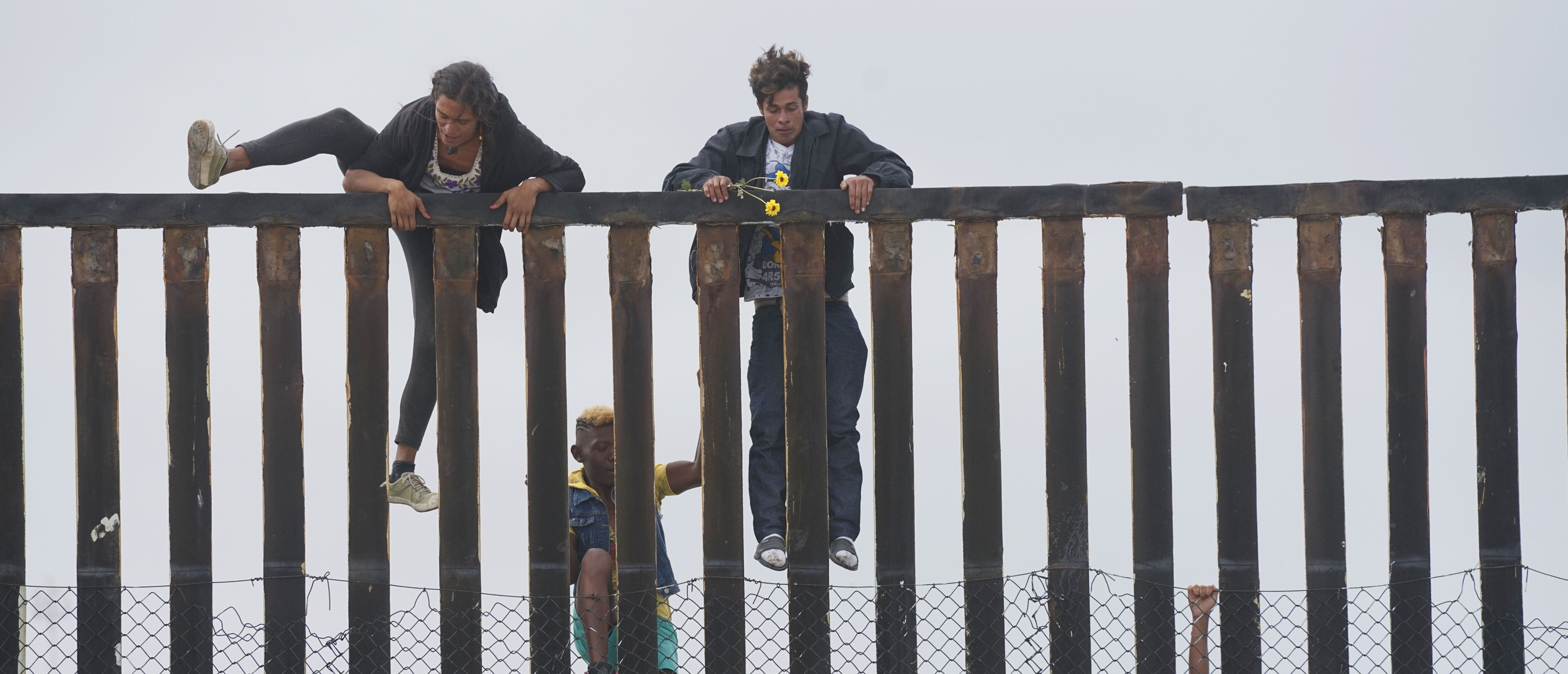 Migrant caravan demonstrators climb the US-Mexico border fence during a rally ... SANDY HUFFAKER/AFP/Getty Images