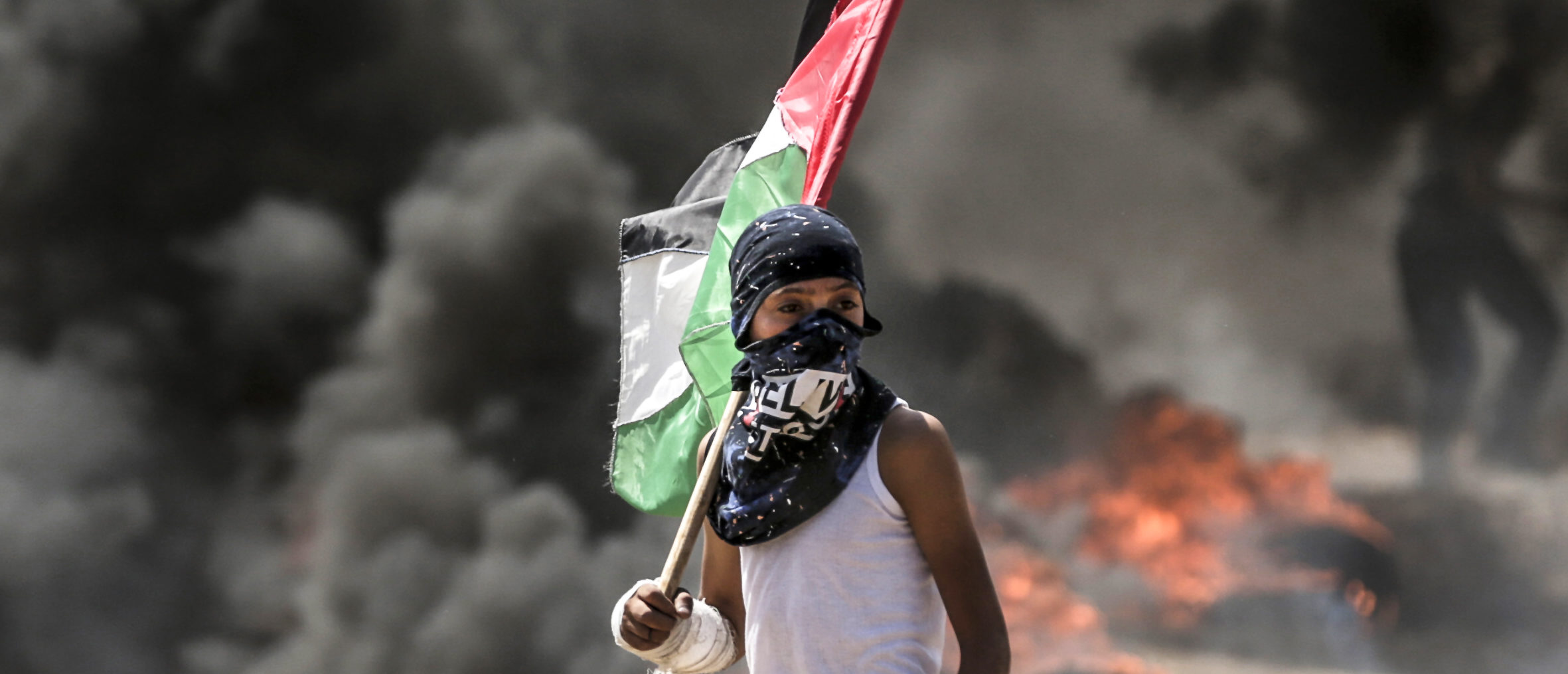 A Palestinian boy holding his national flag looks at clashes with Israeli security forces near the border between the Gaza Strip and Israel east of Gaza City on May 14, 2018, as Palestinians protest over the inauguration of the US embassy following its controversial move to Jerusalem. - Dozens of Palestinians were killed by Israeli fire on May 14 as tens of thousands protested and clashes erupted along the Gaza border against the US transfer of its embassy to Jerusalem, after months of global outcry, Palestinian anger and exuberant praise from Israelis over President Donald Trump's decision tossing aside decades of precedent. (MAHMUD HAMS/AFP/Getty Images)