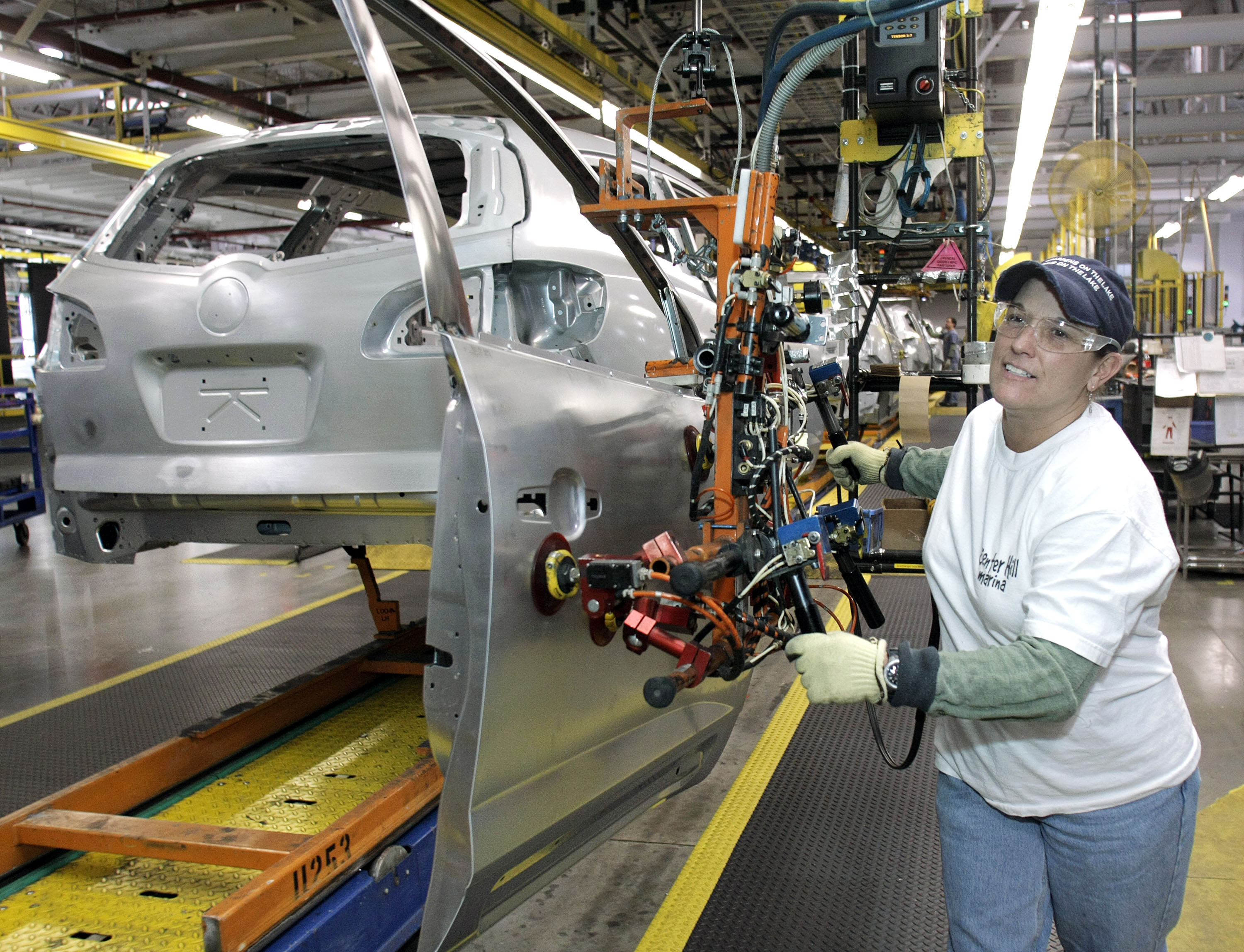 A worker installs a door on a GM crossover SUV as it goes through the assembly line at the General Motors Lansing Delta Township Assembly Plant on March 10, 2010 in Lansing, Michigan. The Delta plant has more than 3,000 workers on two shifts and is expected to add a third shift of 900-1,000 workers in April. The plant produces the Buick Enclave, Chevrolet Traverse, and GMC Acadia crossover SUVs. (Photo by Bill Pugliano/Getty Images)