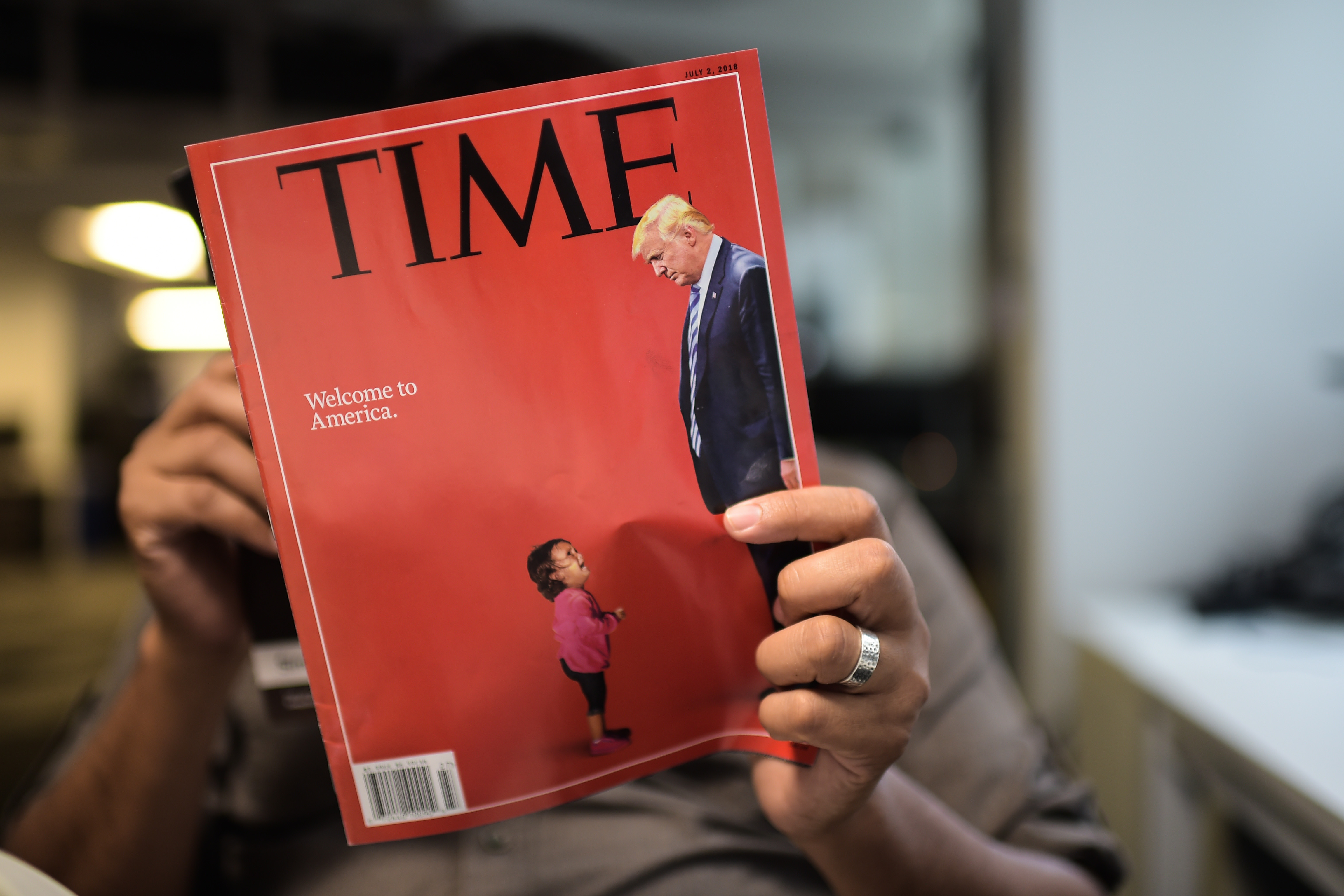 An AFP journalists reads a copy of Time Magazine with a front cover using a combination of pictures showing a crying child taken at the US Border Mexico and a picture of US President Donald Trump looking down, on June 22, 2018 in Washington DC. (Photo credit should read ERIC BARADAT/AFP/Getty Images)