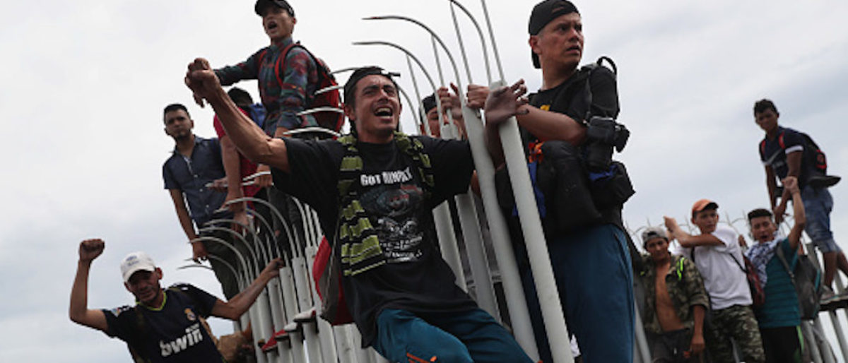 CIUDAD TECUN UMAN, GUATEMALA - OCTOBER 19: Members of the migrant caravan cheer as fellow immigrants clash with Mexican riot police at the border between Mexico and Guatemala on October 19, 2018 in Ciudad Tecun Uman, Guatemala. Migrants and police faced off when the caravan of thousands of migrants tried to cross into Mexico after pushing past Guatemalan security forces. (Photo by John Moore/Getty Images)