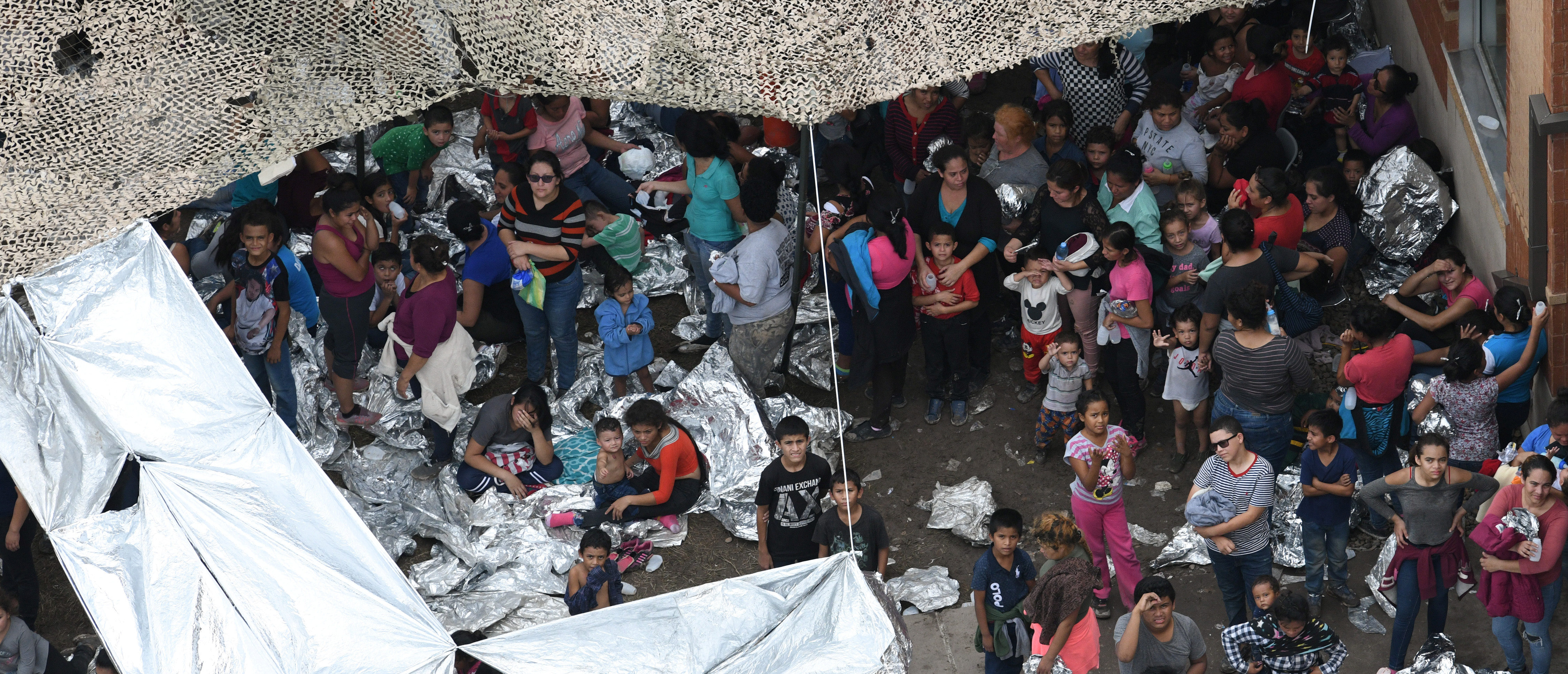 Migrants are seen outside the U.S. Border Patrol McAllen Station in a makeshift encampment in McAllen