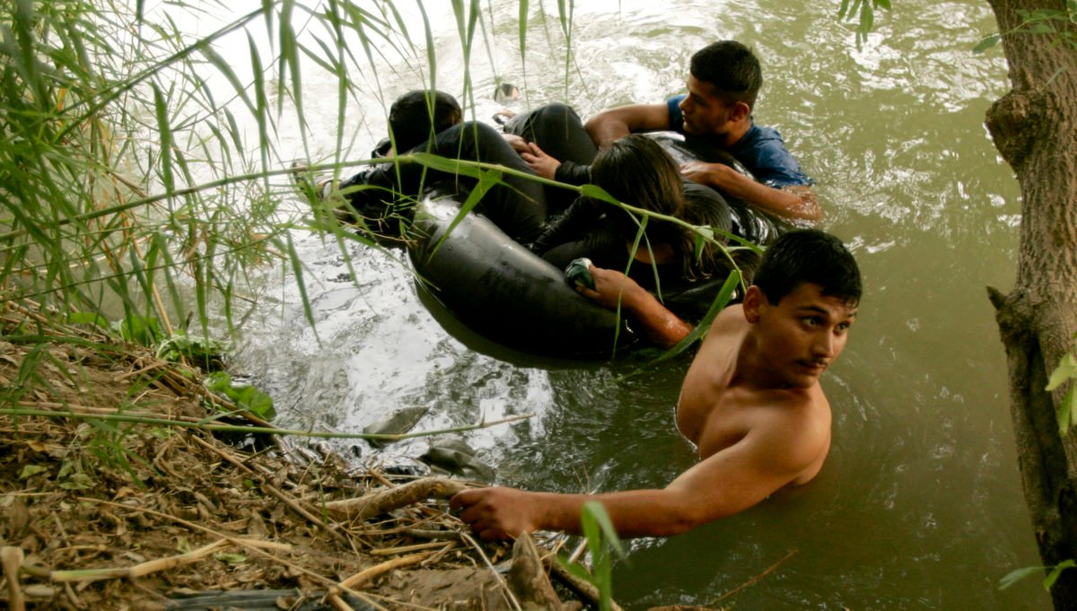 Illegal aliens wait on US side of Rio Grande river in Laredo. REUTERS/Rick Wilking