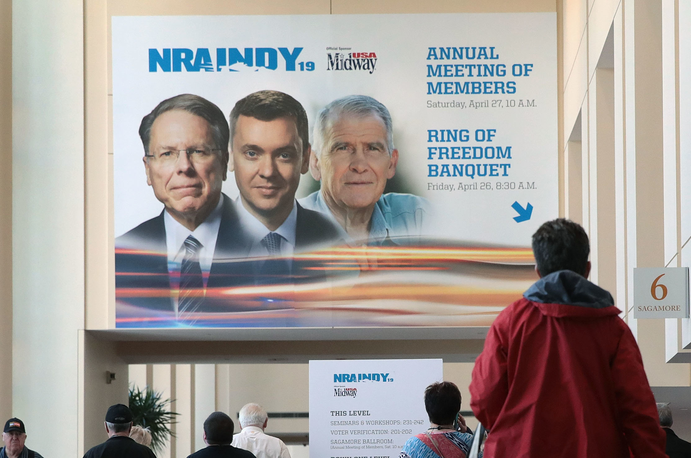 Guest walk under a poster featuring Wayne LaPierre (L), NRA vice president and CEO, Chris Cox (C), executive director of the NRA-ILA, and NRA president Oliver North outside a conference room where the NRA annual meeting of members was being held at the 148th NRA Annual Meetings & Exhibits on April 27, 2019 in Indianapolis, Indiana. Only LaPierre remains. (Photo by Scott Olson/Getty Images)