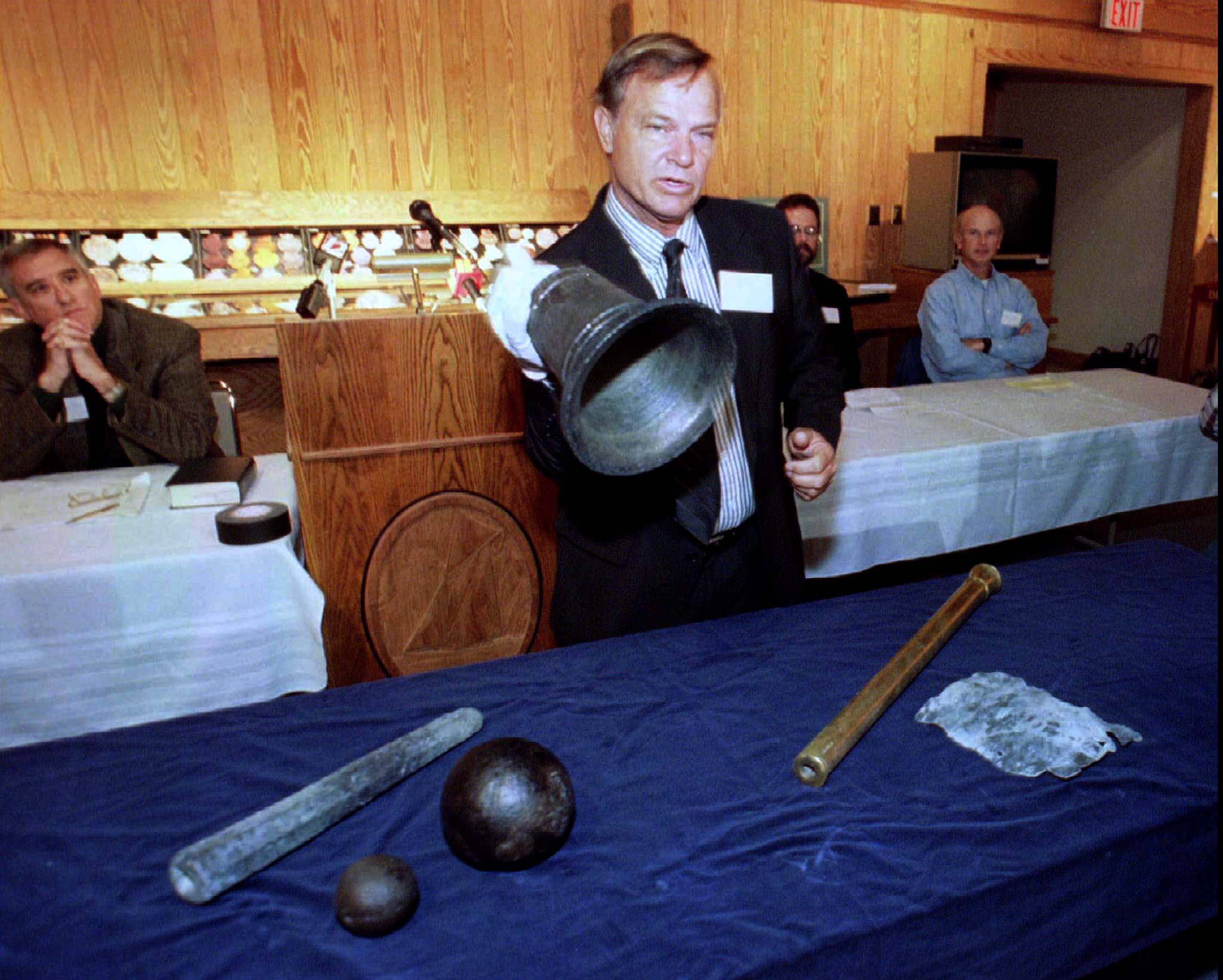"Mike Davis, president of the Maritime Research Institute, hoists a bronze bell recovered from the wreckage of Blackbeard's pirate ship ""Queen Anne's Revenge,"" on October 29, 1997. (Reuters)"