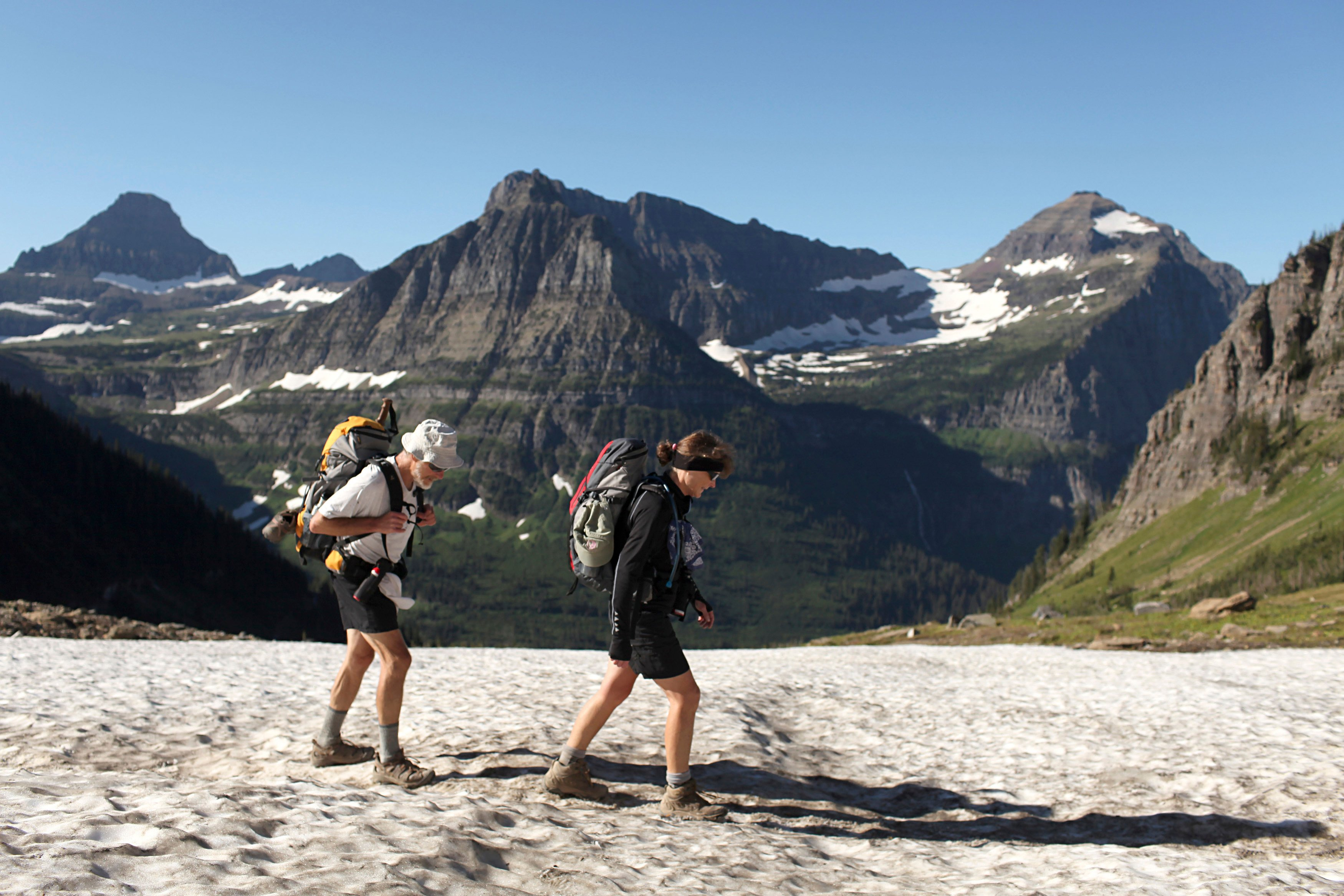 Hikers trek through snow along the Highline Trail in Glacier National Park, Montana