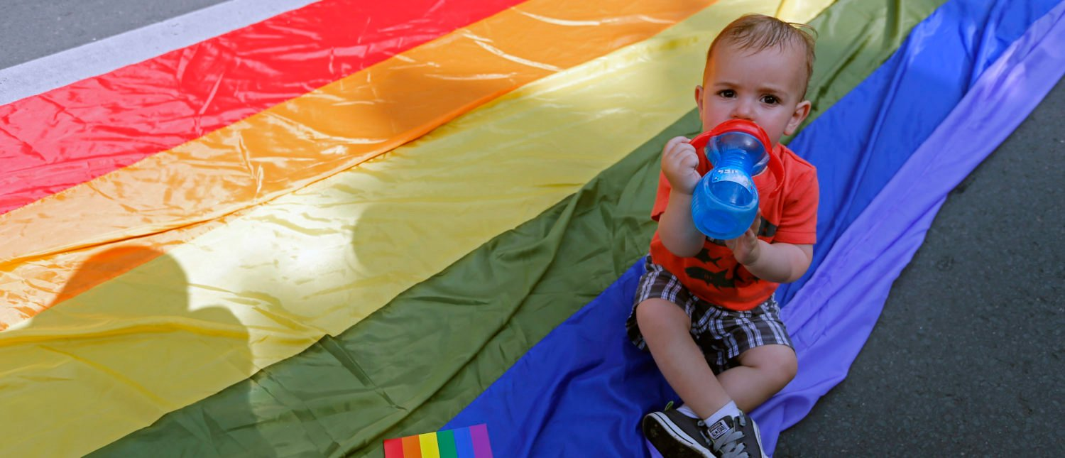 A child drinks water on the rainbow flag during Romania's gay community Gay Fest 2014 pride parade in Bucharest June 7, 2014. REUTERS/Bogdan Cristel (ROMANIA - Tags: SOCIETY) - GM1EA68019801
