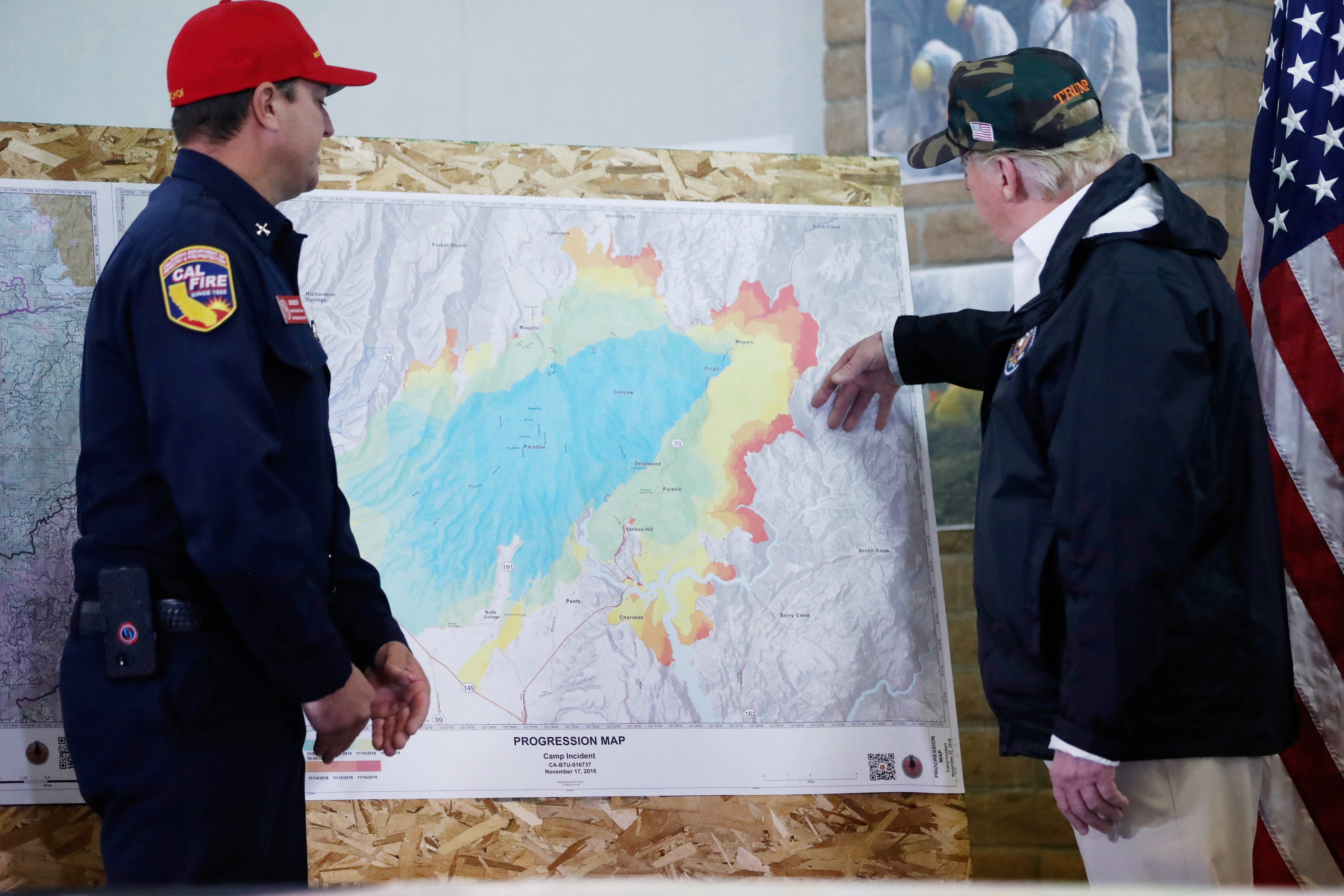 President Donald Trump views the map with Josh Bischof after visiting the charred wreckage of in Paradise California