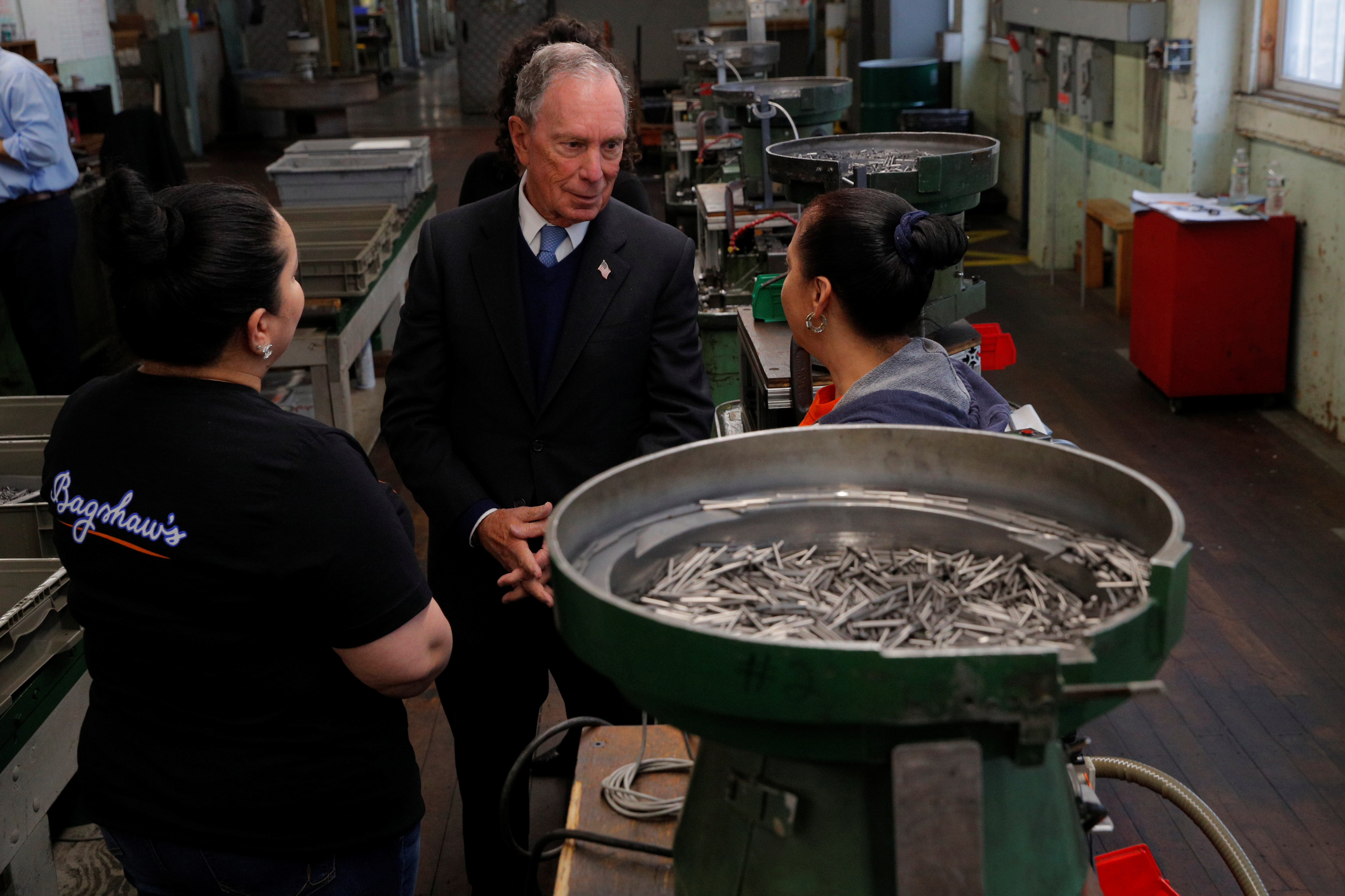 Former New York City Mayor Bloomberg talks to workers during a tour of WH Bagshaw Company in Nashua